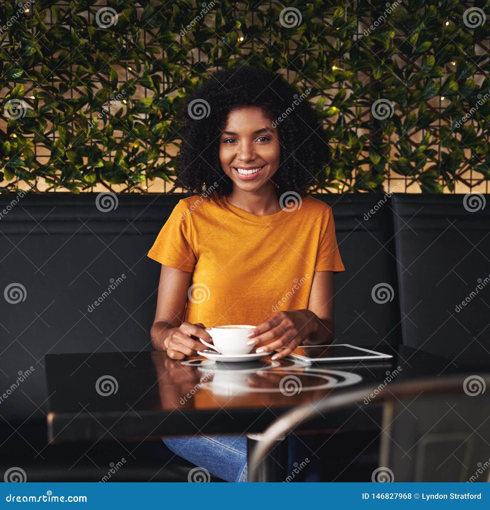 Retrato de uma jovem mulher de sorriso que senta-se no café