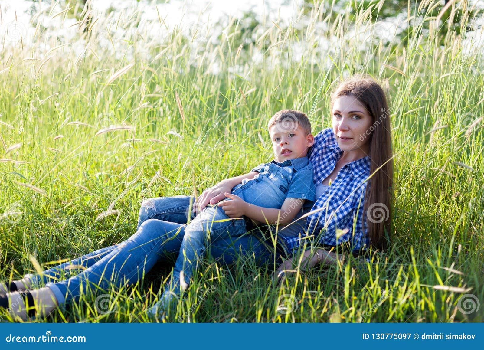Retrato de uma mãe bonita com um curso novo do ar livre do filho