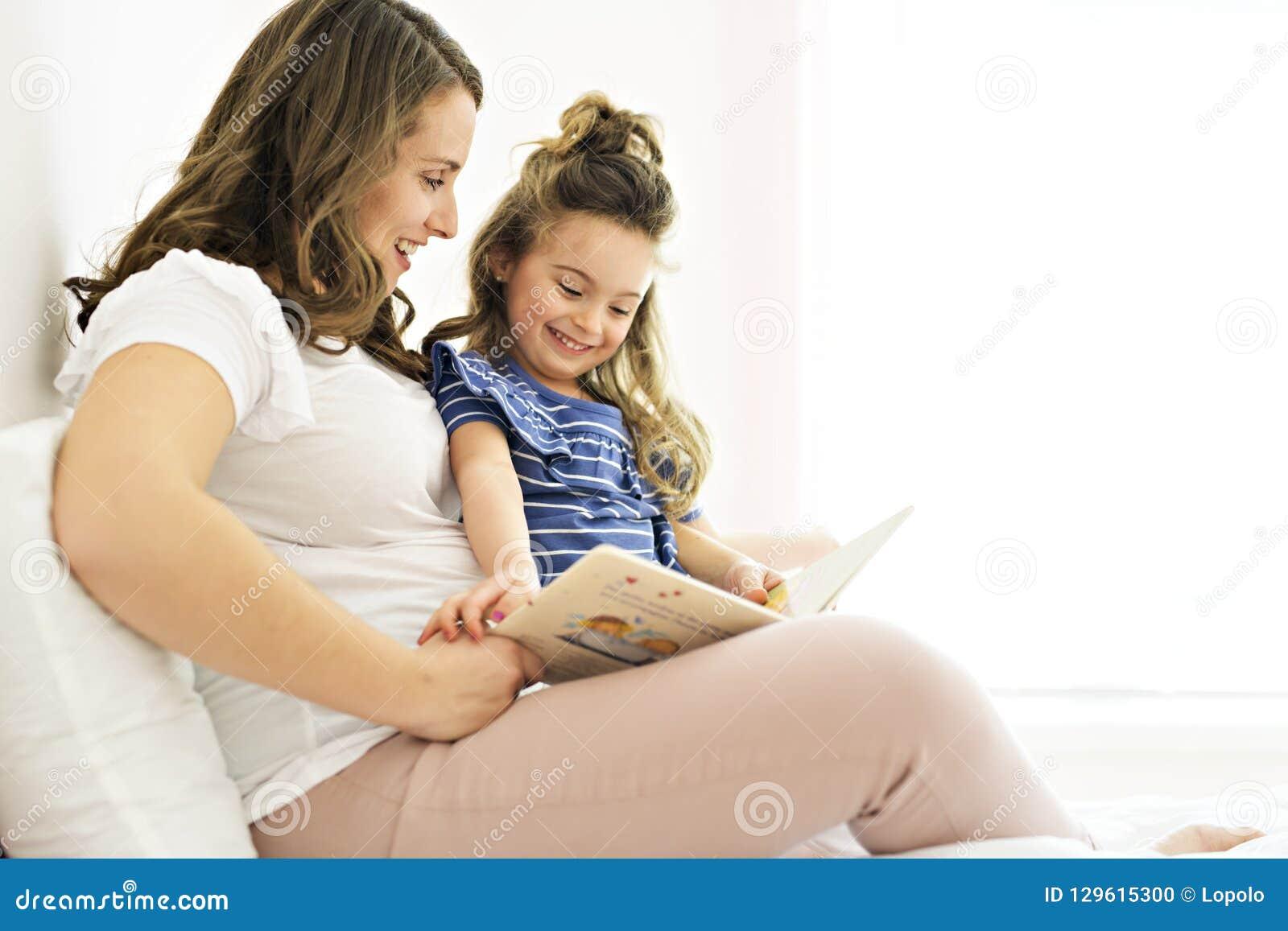 Retrato de uma mãe e de uma filha que leem um livro que encontra-se e para relaxar na cama