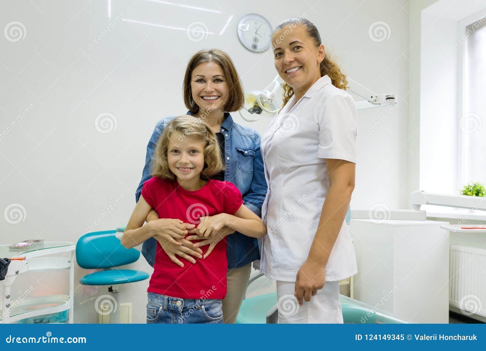 Retrato de uma mãe feliz com criança e dentista do doutor, no escritório dental