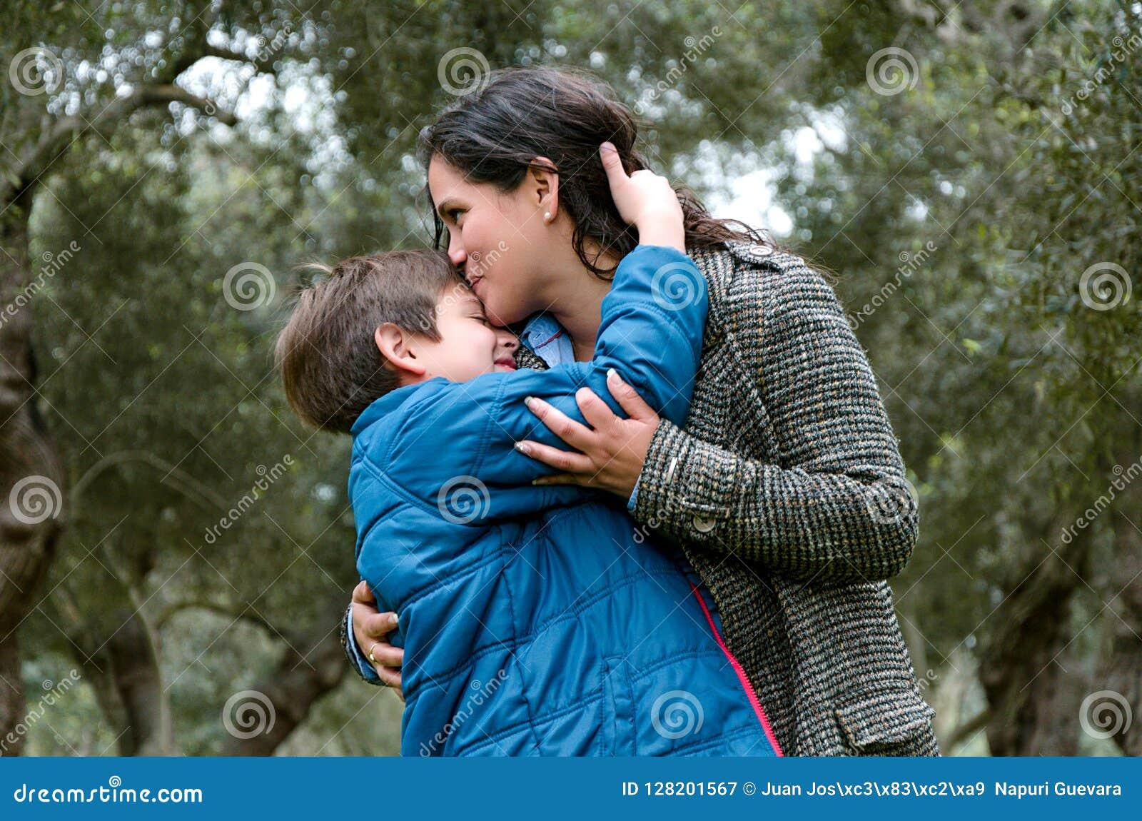 Retrato de uma mãe que beija seu filho pequeno no parque