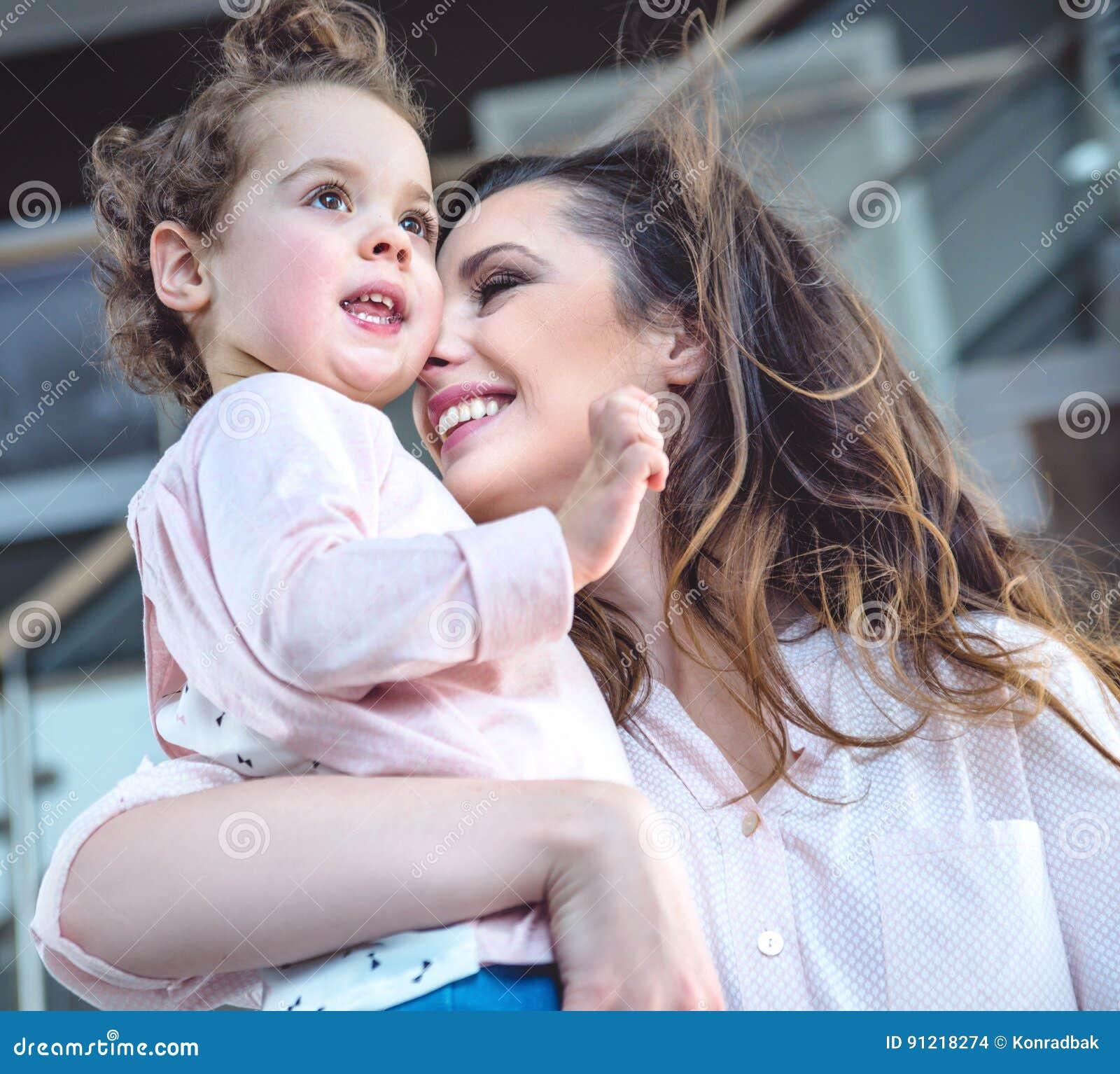 Retrato de uma mamã alegre que afaga a criança amado