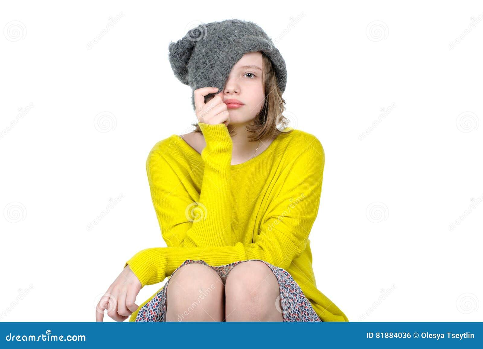 Retrato de uma menina adolescente bonito, que puxe seu tampão sobre sua cara