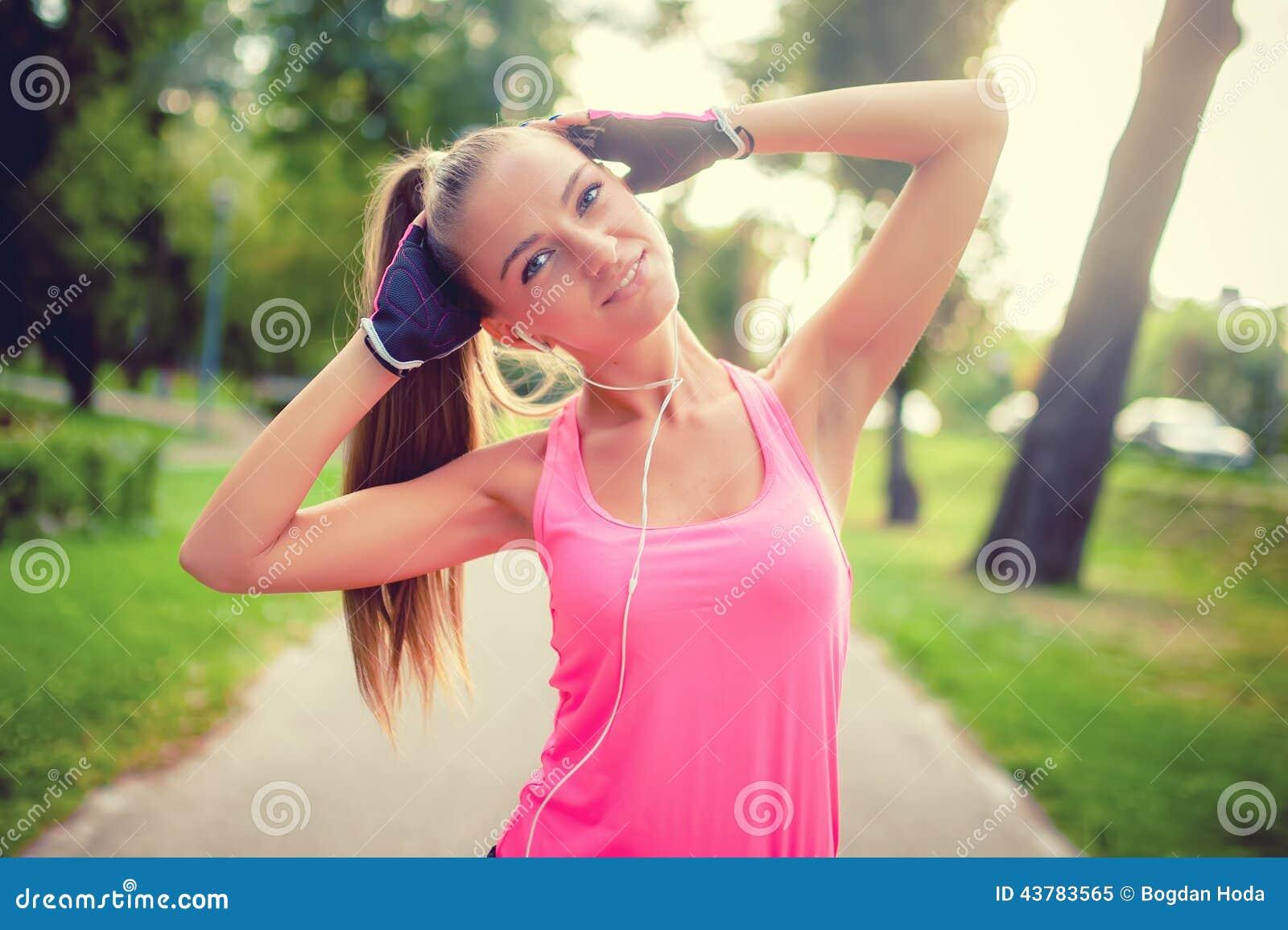 Retrato de uma menina atlética que dá certo e que estica no parque