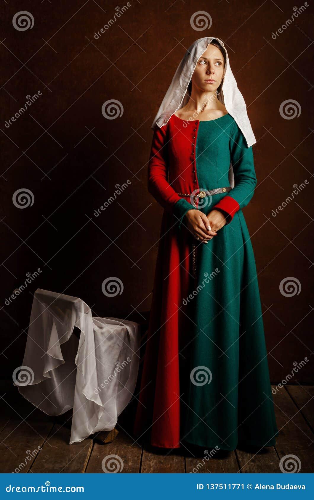 Retrato de uma menina bonita em um vestido medieval em vermelho e em verde em um fundo marrom