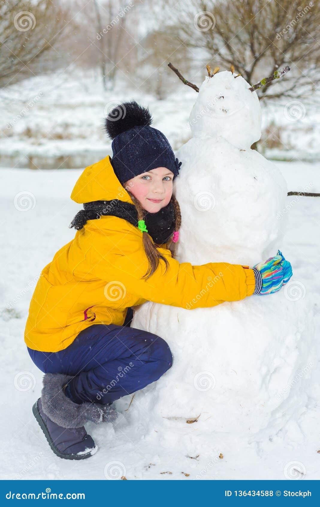 Retrato de uma menina bonita no inverno a criança feliz faz um boneco de neve