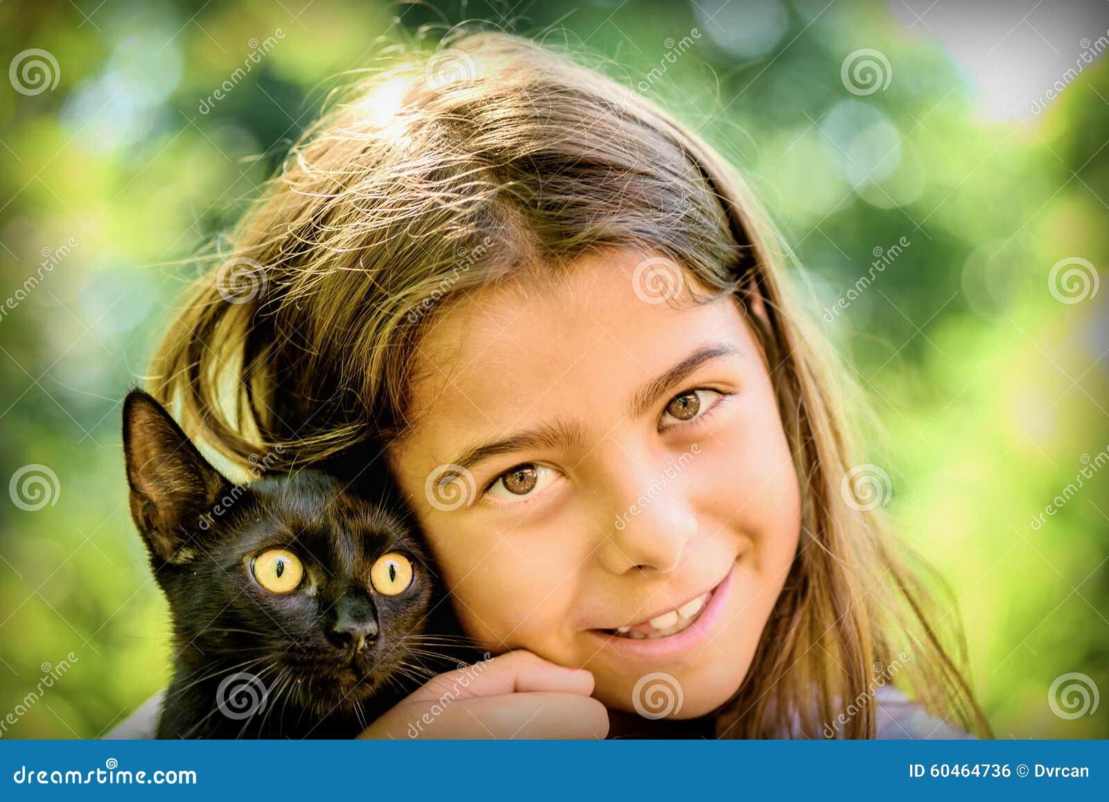 Retrato de uma menina bonita que guarda um gato preto