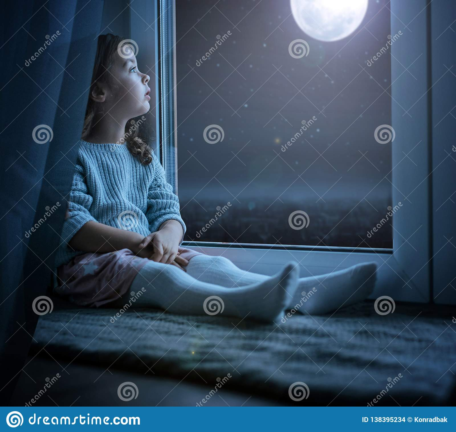 Retrato de uma menina bonito que olha a lua da noite