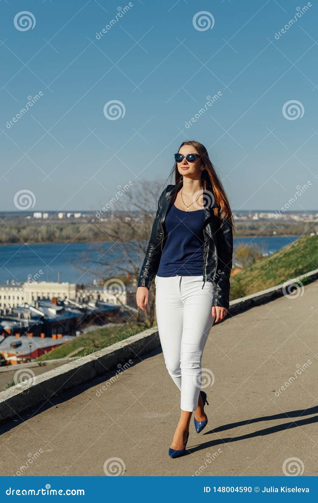 Retrato de uma menina de cabelo escuro ? moda nos ?culos de sol, est? em um casaco de cabedal