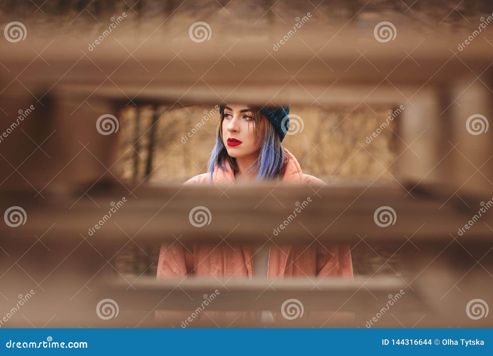 Retrato de uma menina com cabelo colorido no fundo da natureza com algumas placas de madeira borradas no primeiro plano