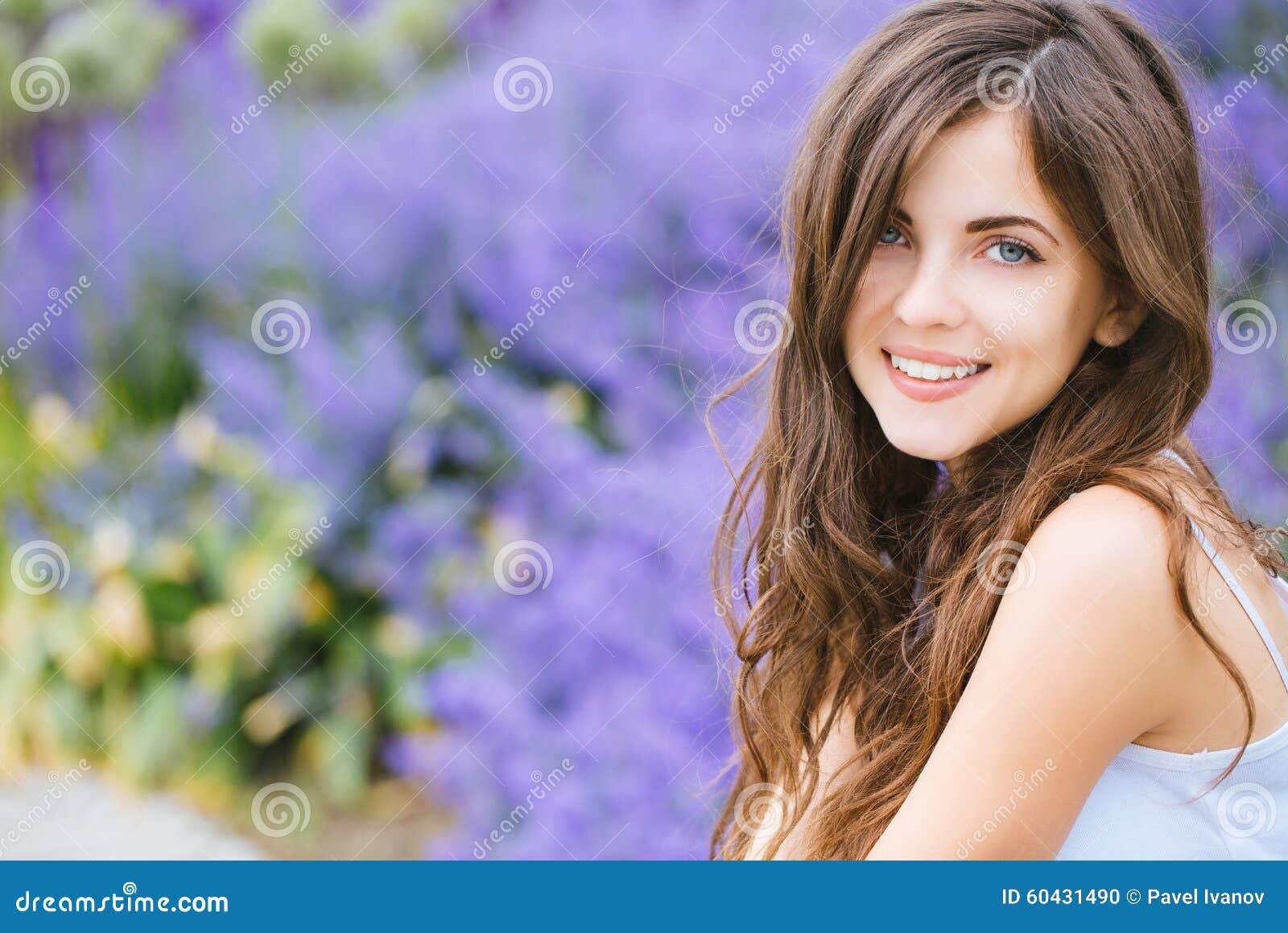 Retrato de uma menina nova bonita do estudante no parque