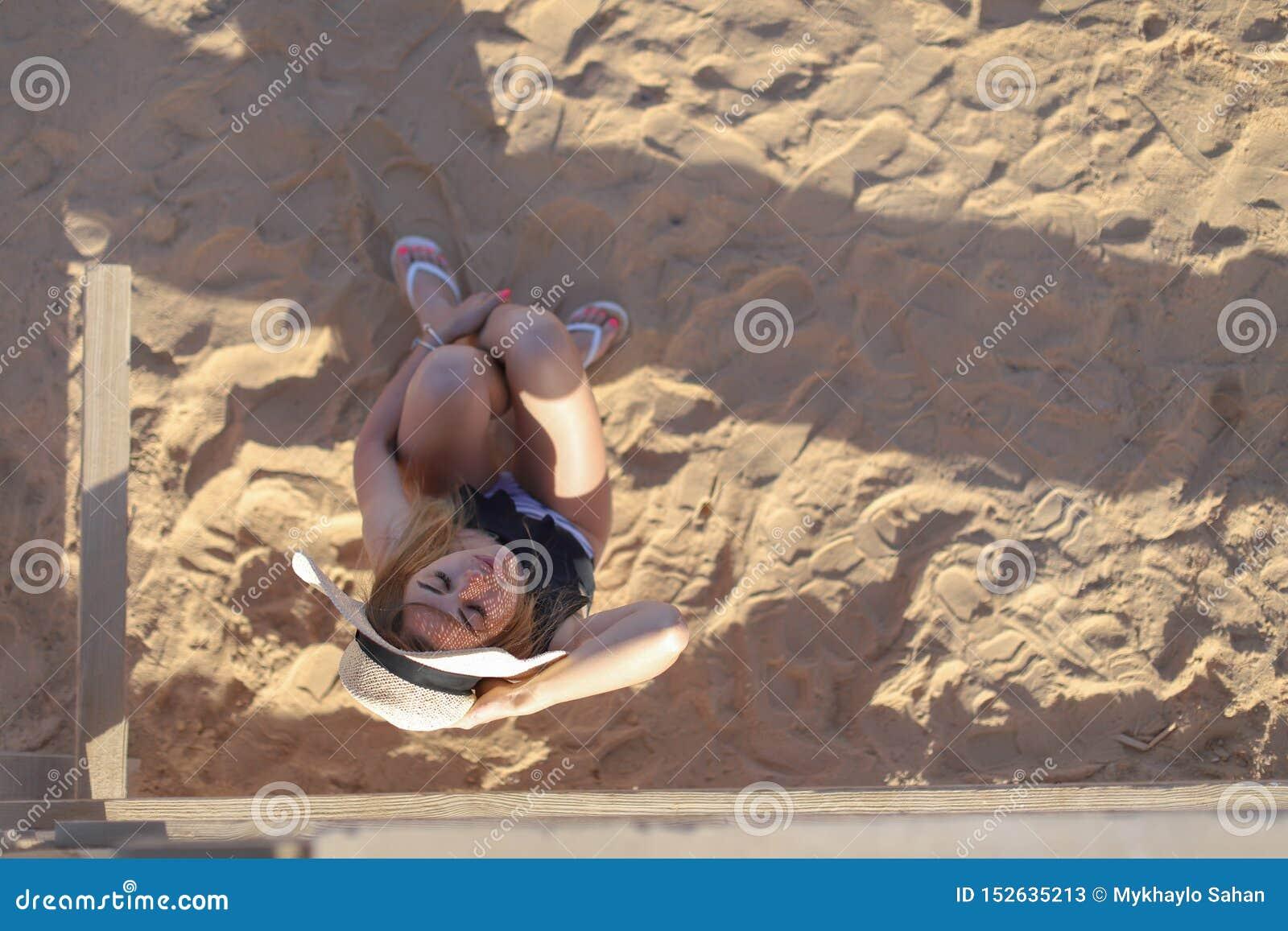 Retrato de uma menina  sexy  bronzeada bonita na praia Mulher que relaxa no roupa de banho na areia Conceito das f?rias de ver?o