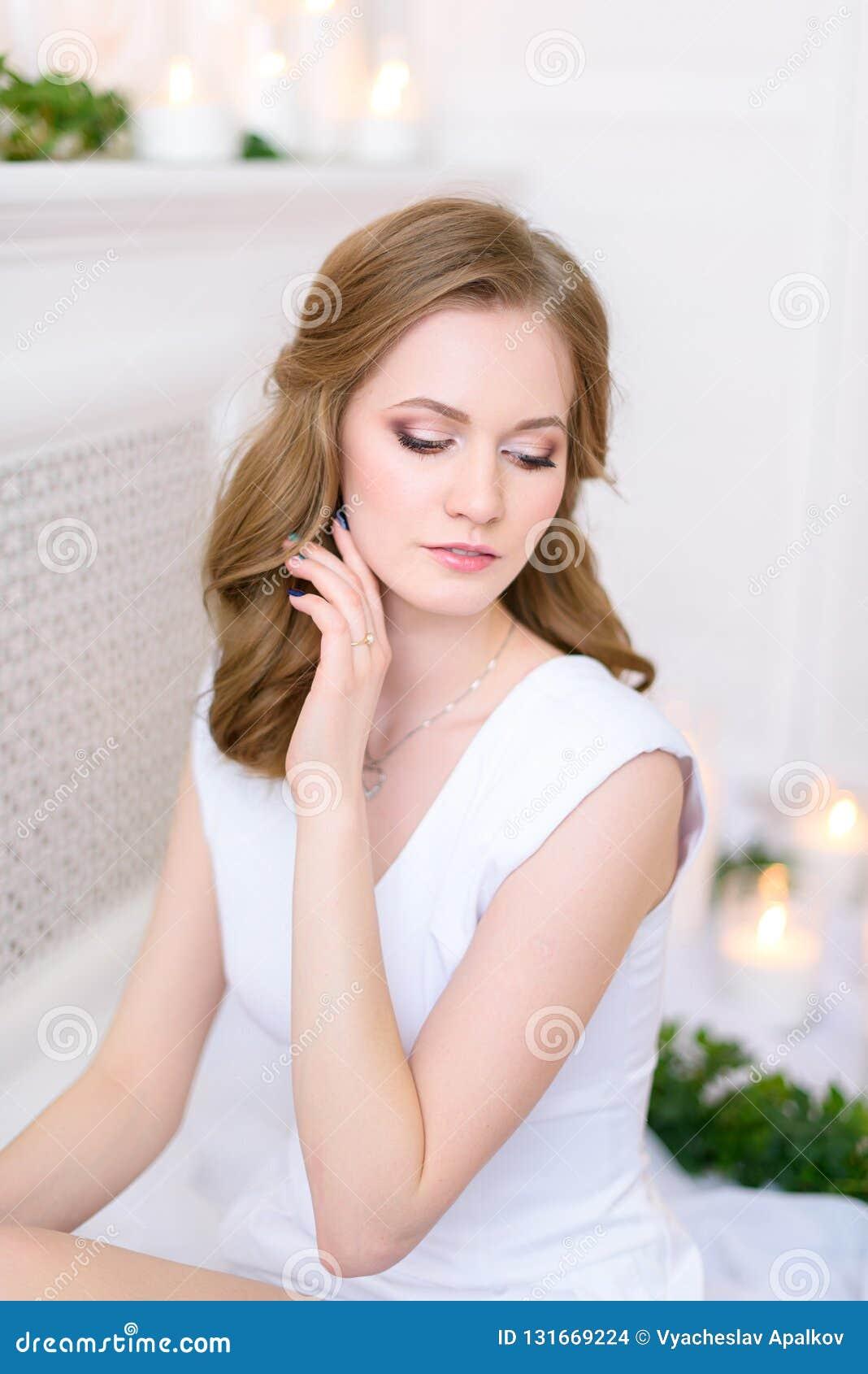 Retrato de uma menina tímida nova em um vestido limpo, sua mão que toca em sua cara delicadamente Mulher moreno nova lindo com em