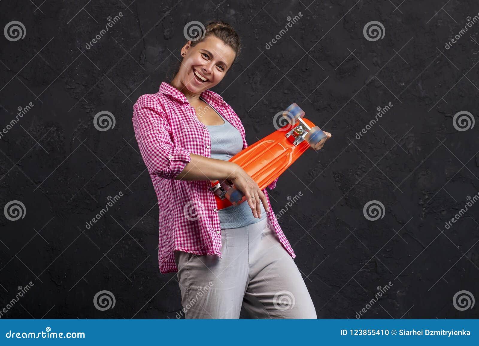 Retrato de uma moça bonita elegante com um skate nas mãos
