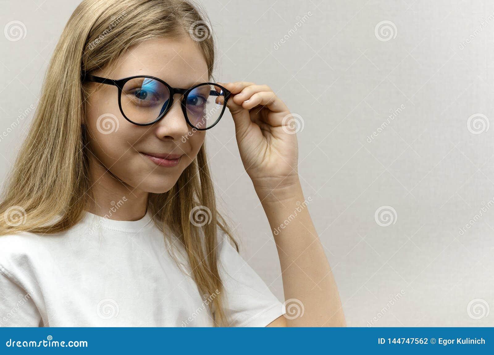 Retrato de uma mo?a bonita de sorriso com vidros Crian?a esperta nerdy