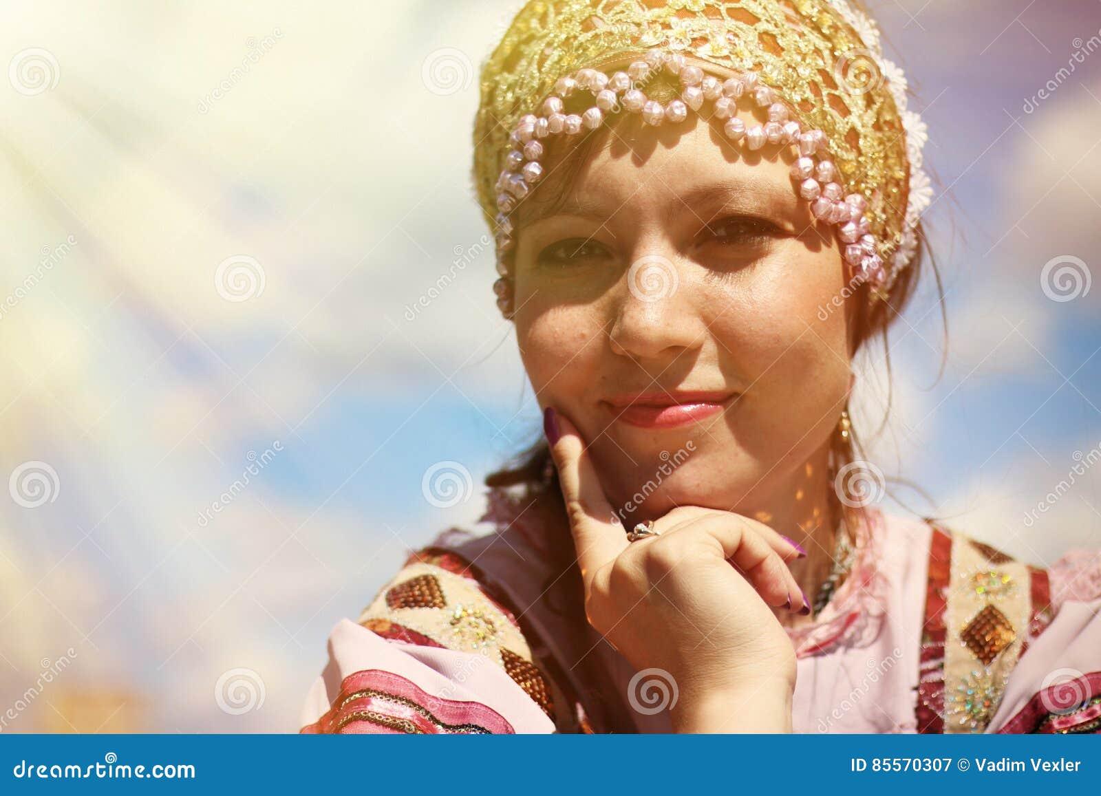 Retrato de uma moça no traje popular do russo no fundo do céu
