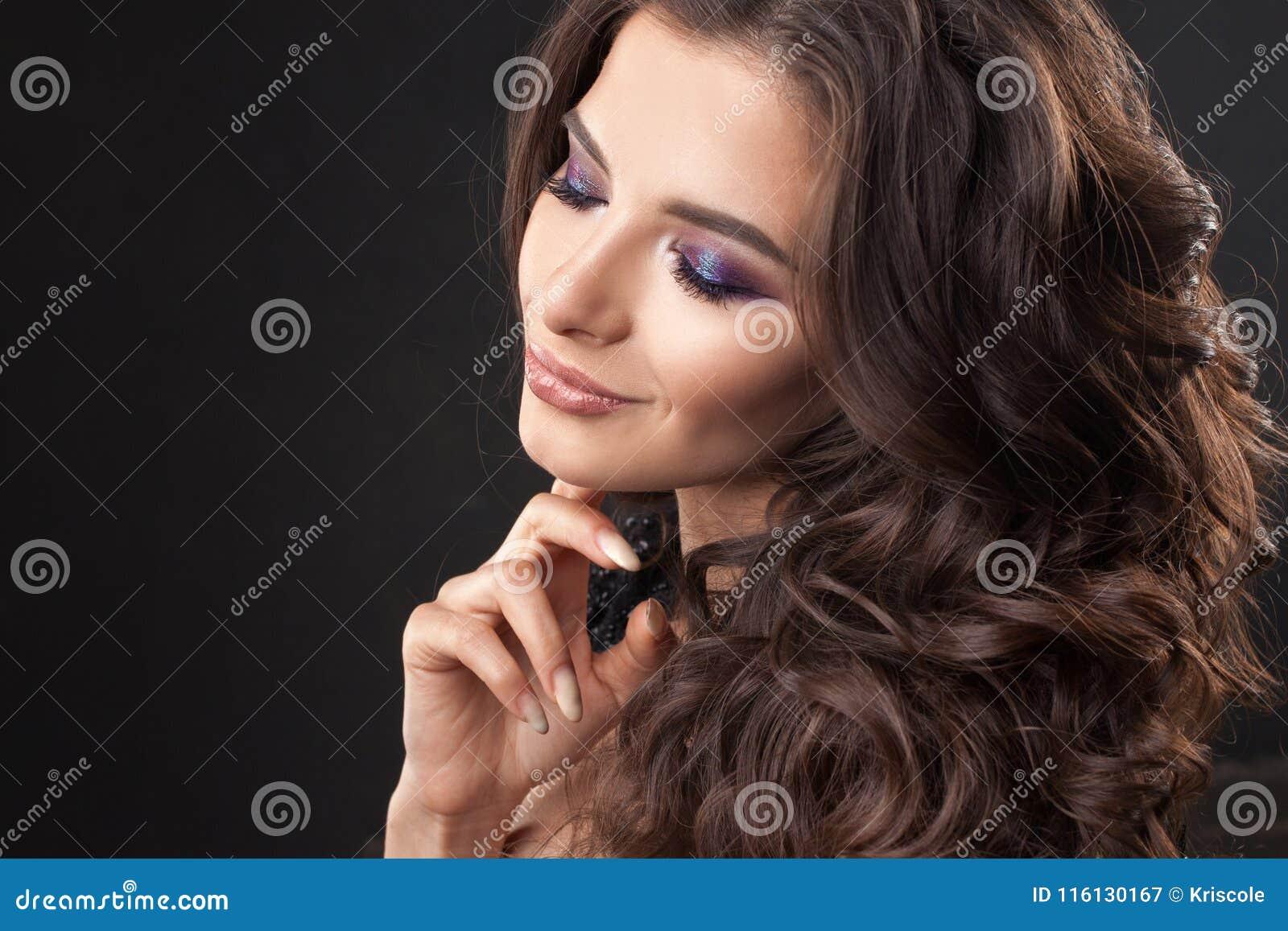Retrato de uma mulher atrativa nova com cabelo encaracolado lindo Brunette atrativo