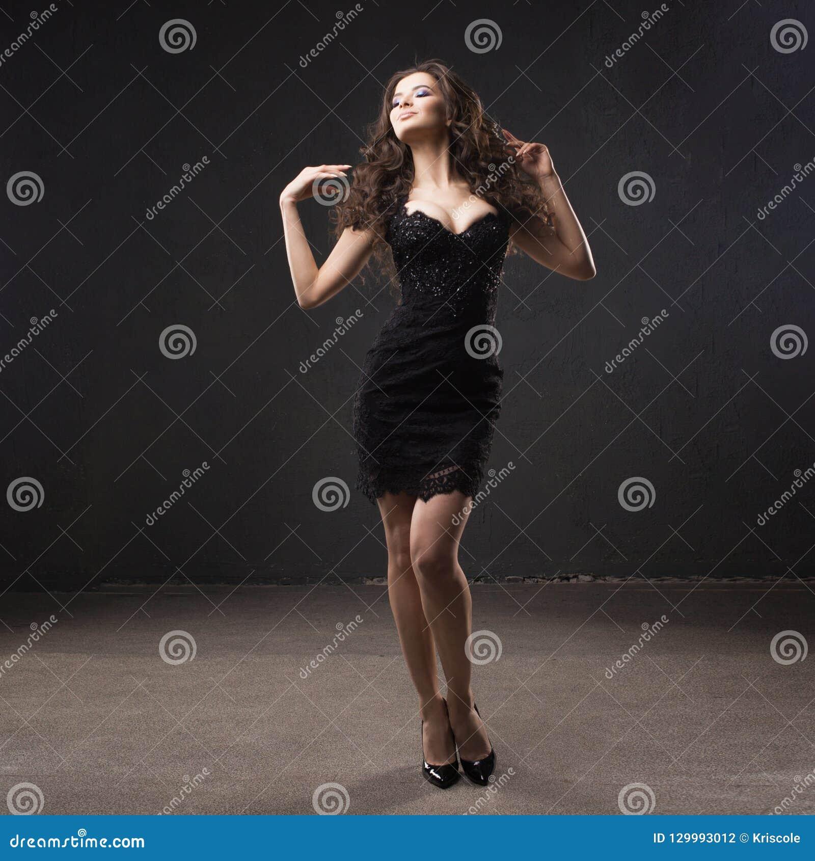 Retrato de uma mulher atrativa nova com cabelo encaracolado lindo morena nova no vestido preto pequeno