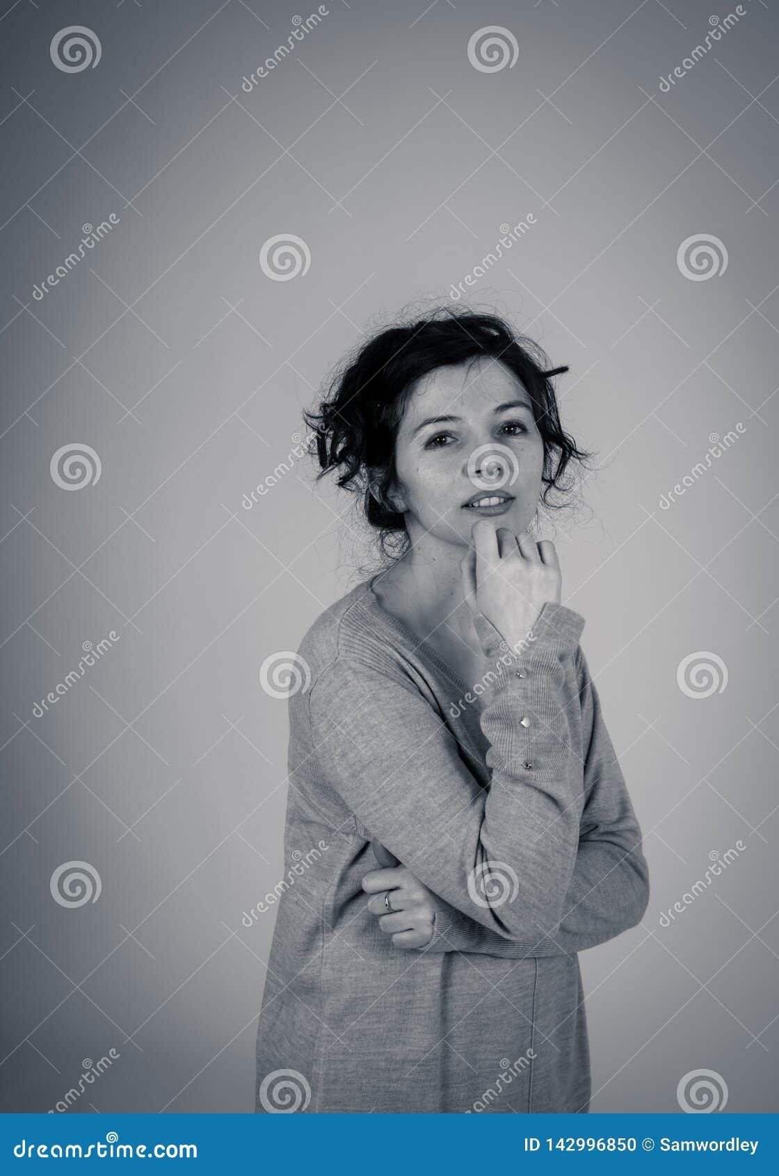 Retrato de uma mulher atrativa nova que toca no seu pensamento do queixo Expressões e emoções humanas