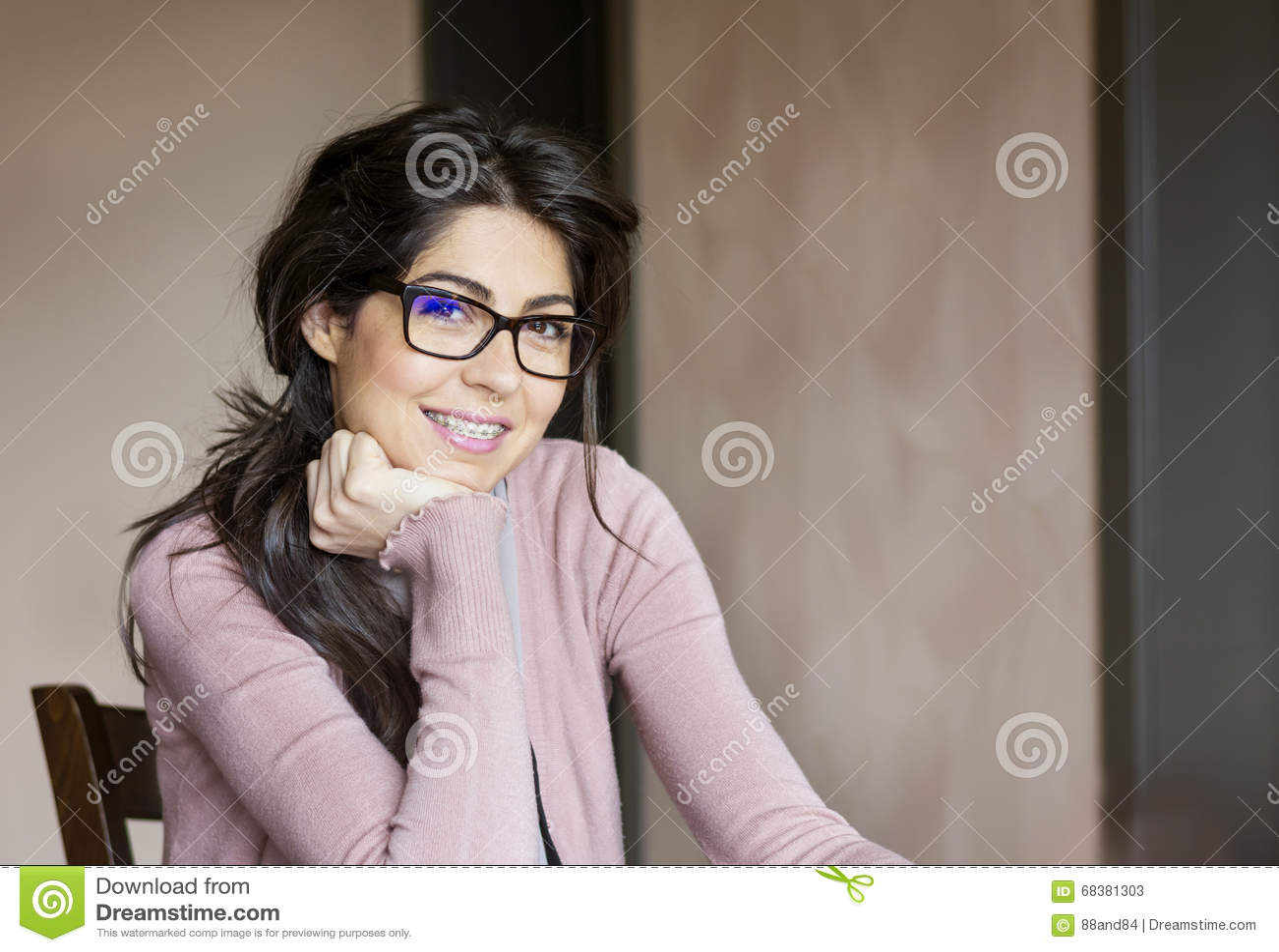 Retrato de uma mulher bonita com as cintas nos dentes Tratamento ortodôntico Conceito dos cuidados dentários