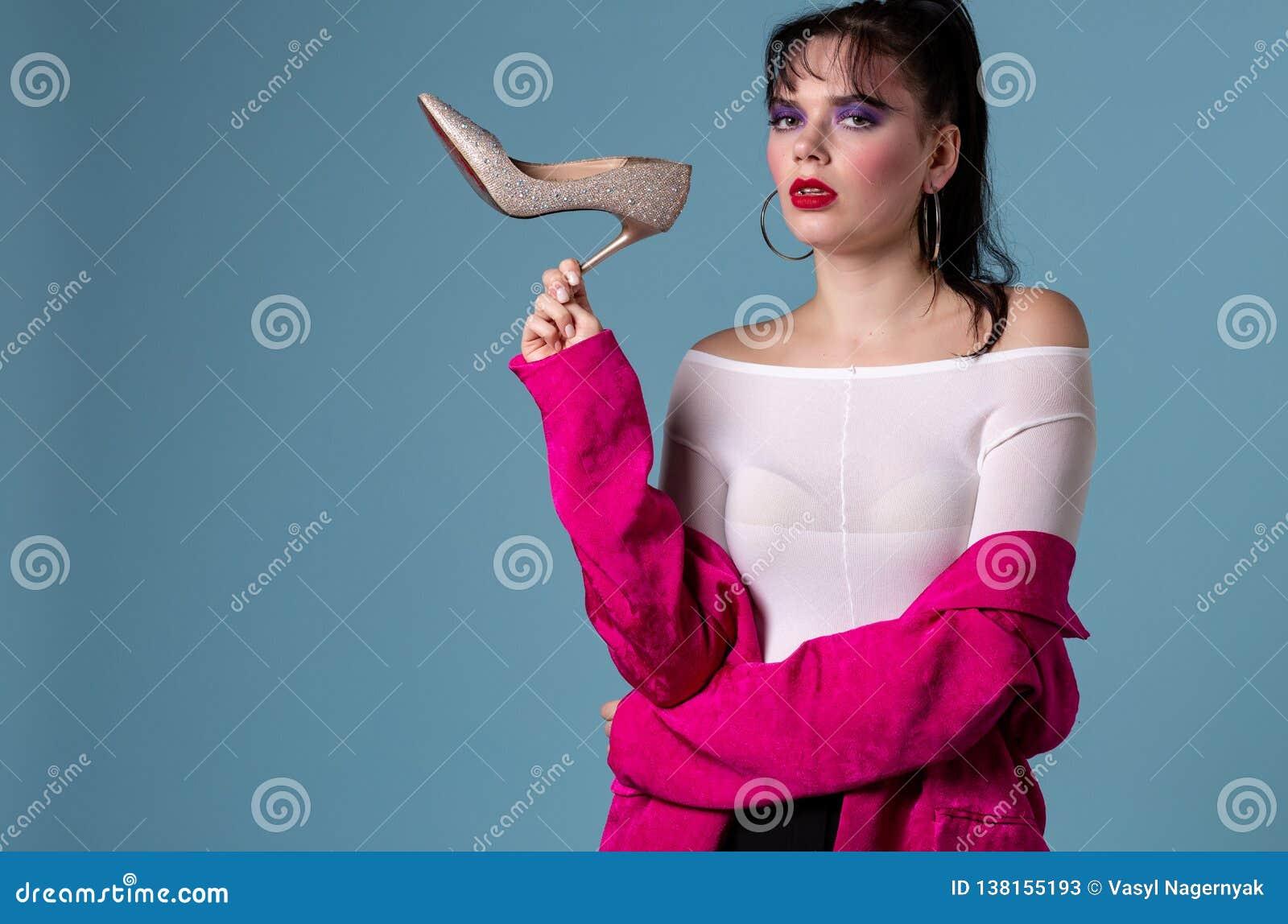 Retrato de uma mulher bonita confusa no revestimento cor-de-rosa que guarda a sapata dos saltos altos