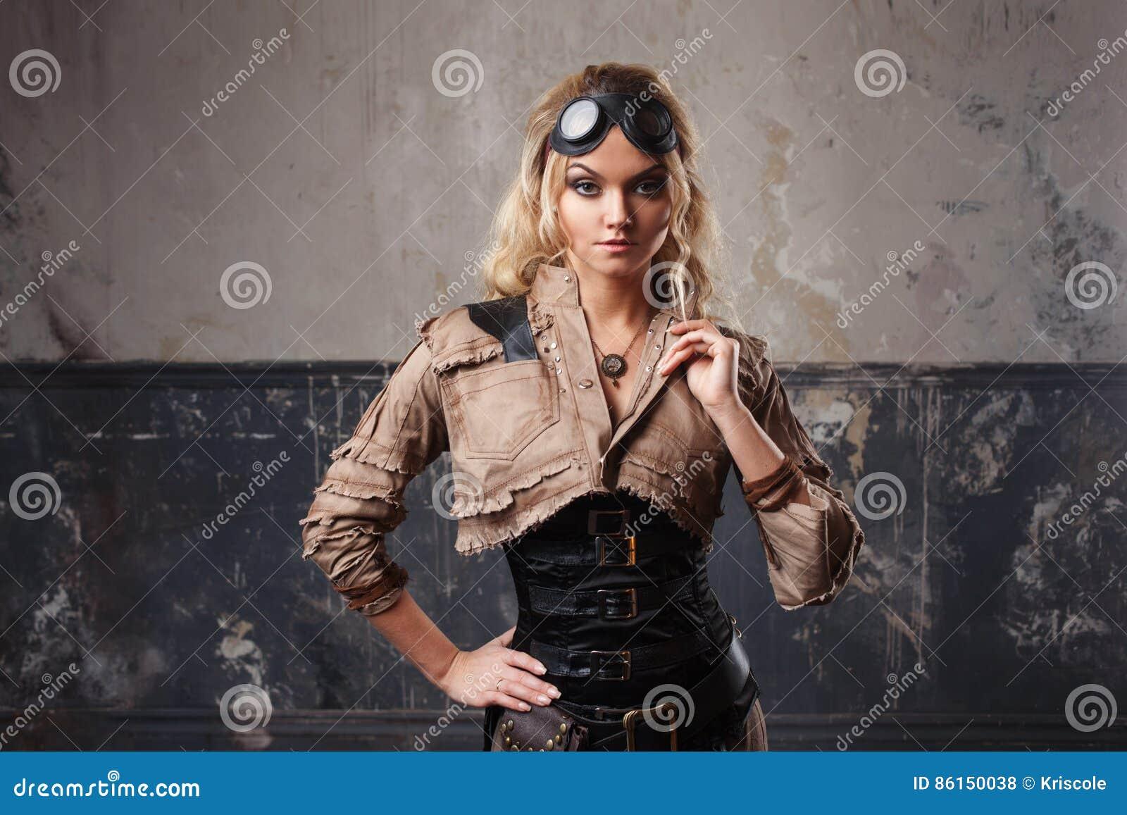 Retrato de uma mulher bonita do steampunk em vidros do aviador sobre o fundo do grunge