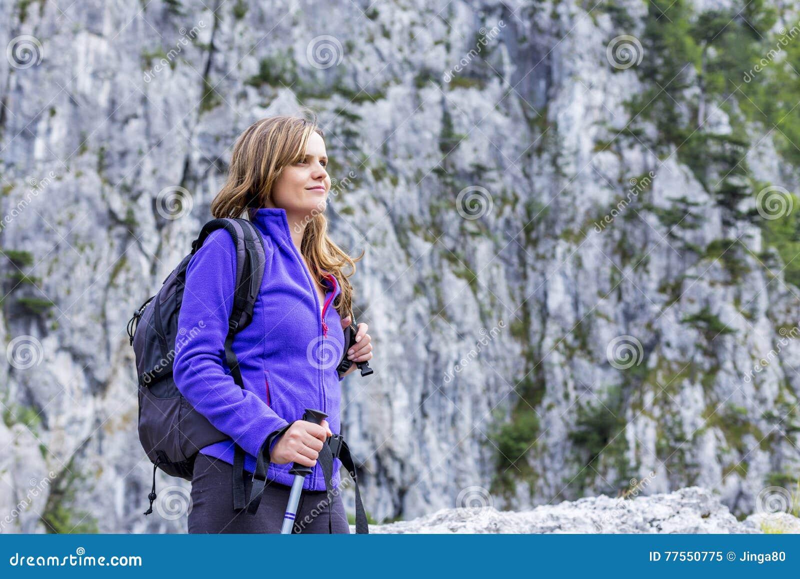 Retrato de uma mulher bonita que guarda a caminhada do polo ao escalar