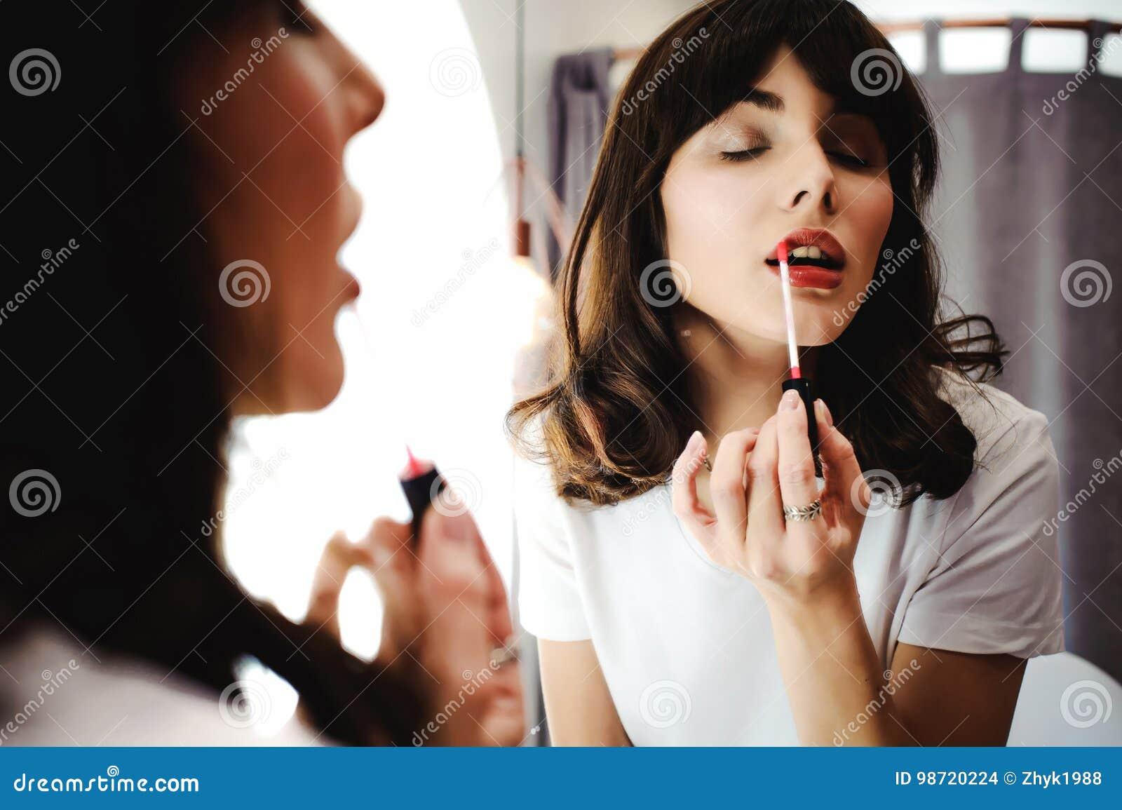 Retrato de uma mulher bonita, tinturas seu rosa do batom dos bordos, olhando no espelho