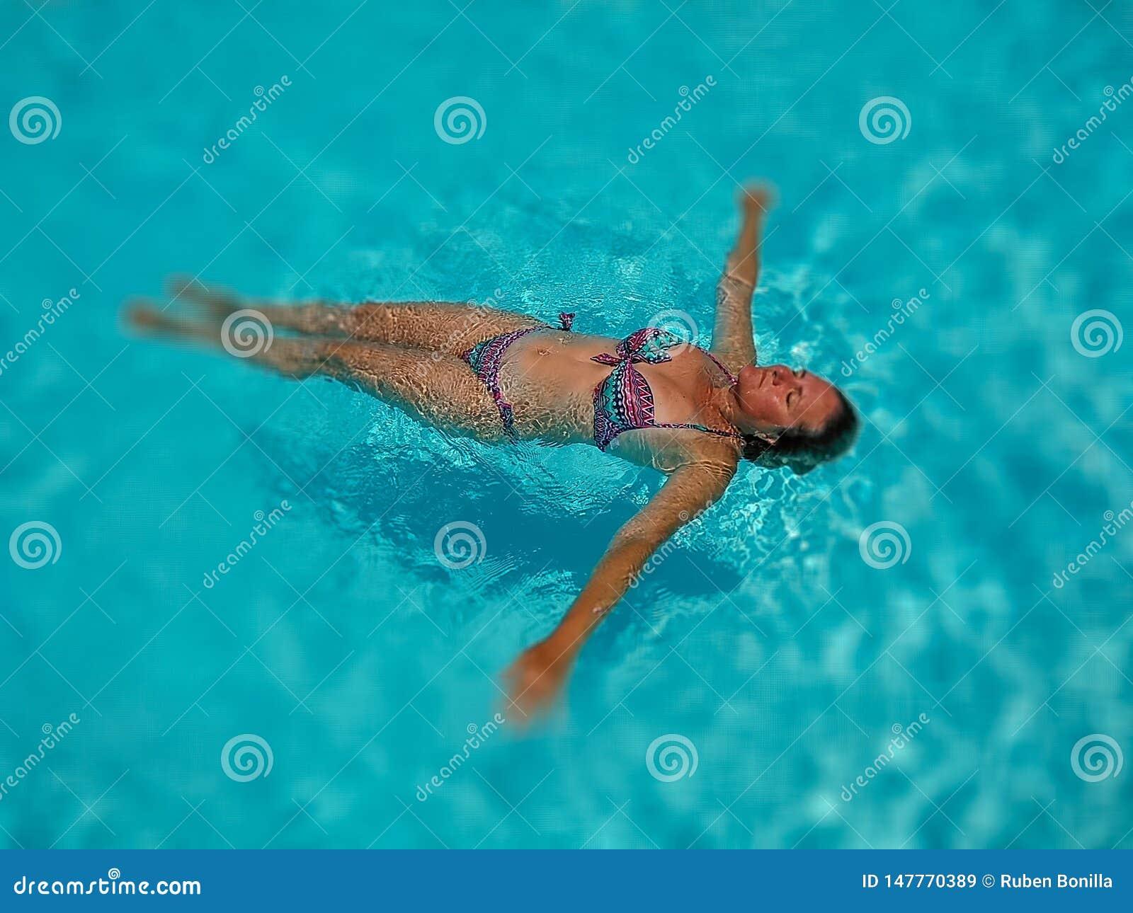 Retrato de uma mulher branca bonita que aprecia uma natação calma de relaxamento do tempo na água transparente de uma associação