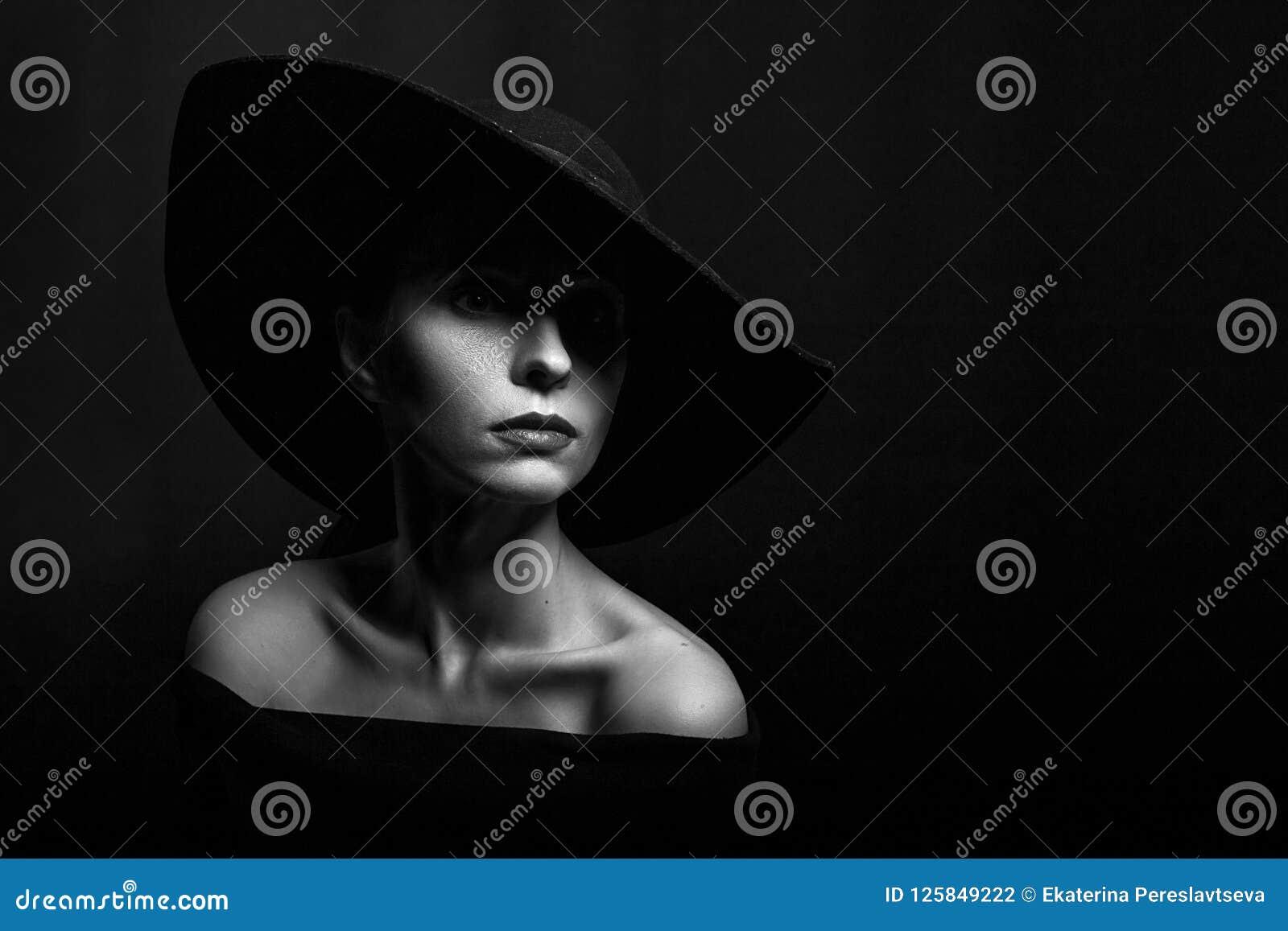 Retrato de uma mulher em um chapéu negro em uma foto preto e branco do fundo preto