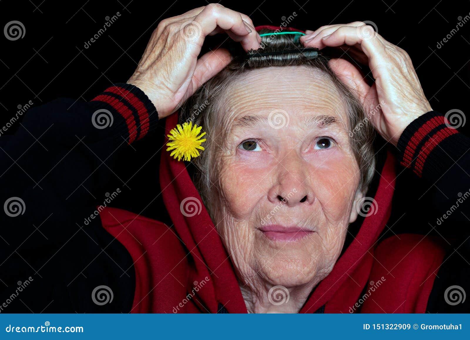 Retrato de uma mulher idosa com o cabelo cinzento que faz seu cabelo e que decora o com uma flor do dente-de-leão