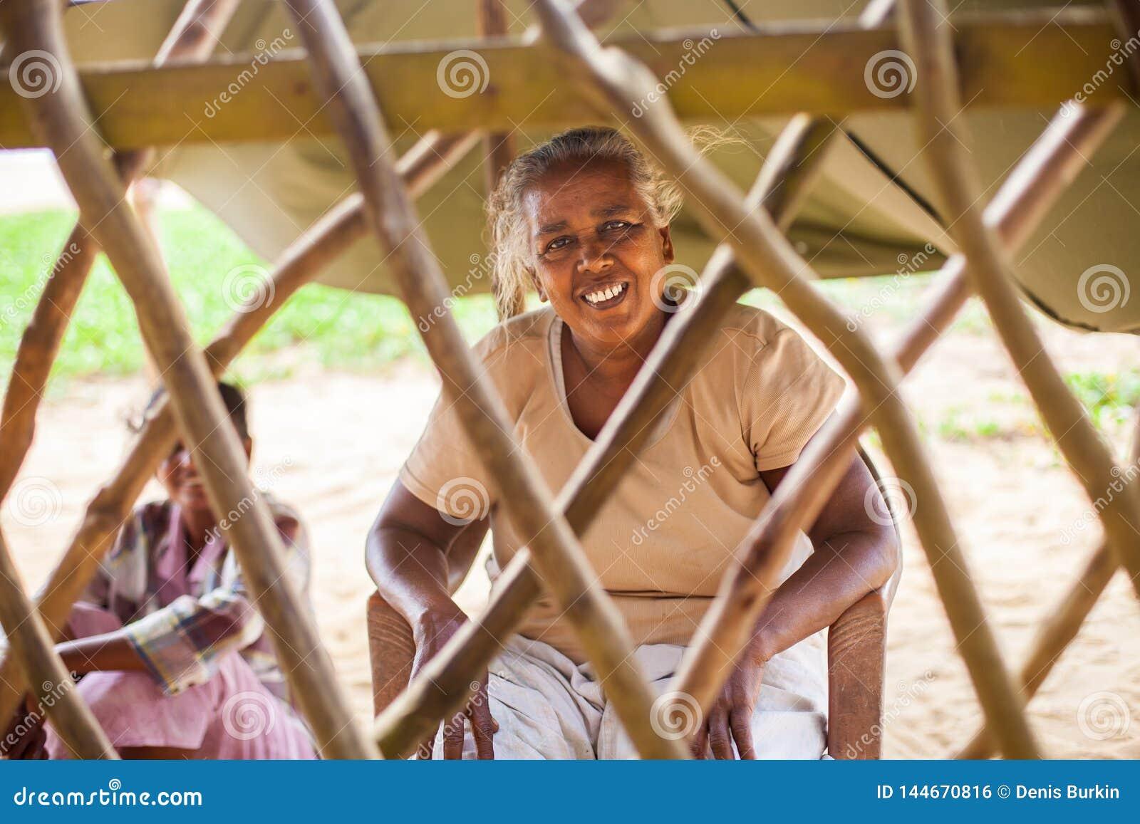 Retrato de uma mulher indiana pobre, idosa atrás de uma cerca sob a forma de uma estrutura