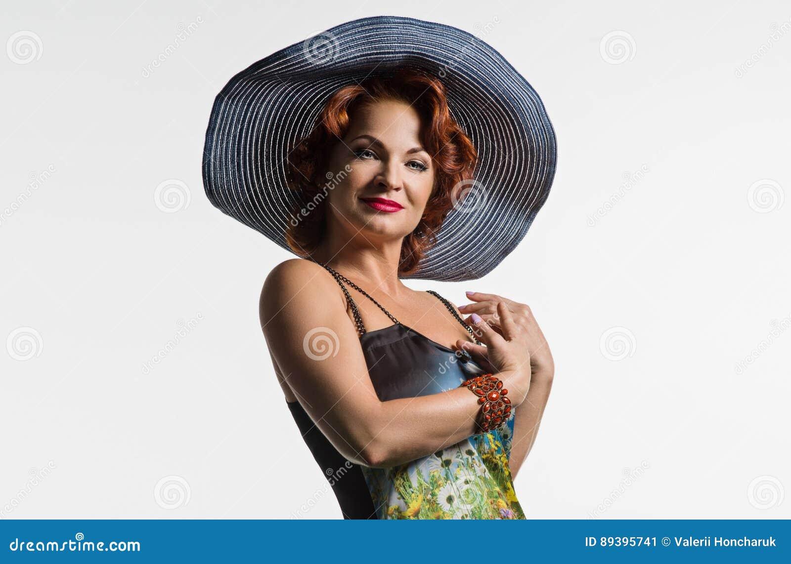 Retrato de uma mulher madura com cabelo vermelho e um chapéu