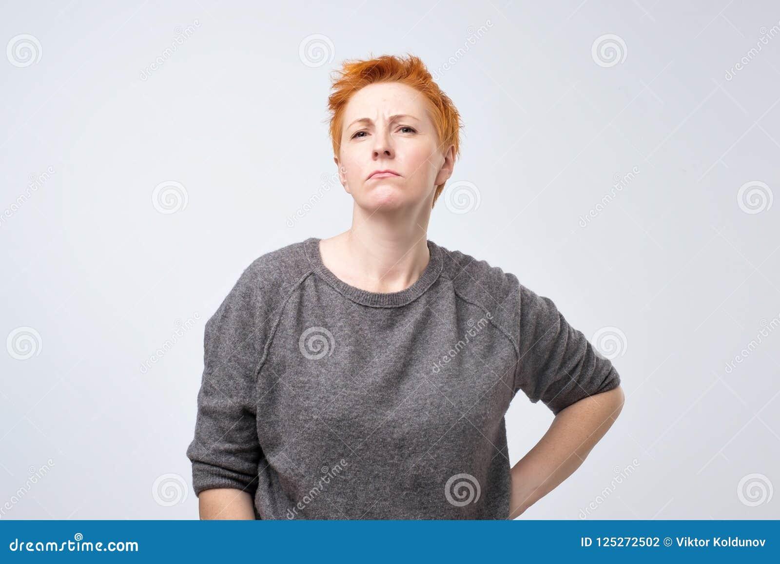 Retrato de uma mulher de meia idade triste com cabelo vermelho curto em um fundo cinzento