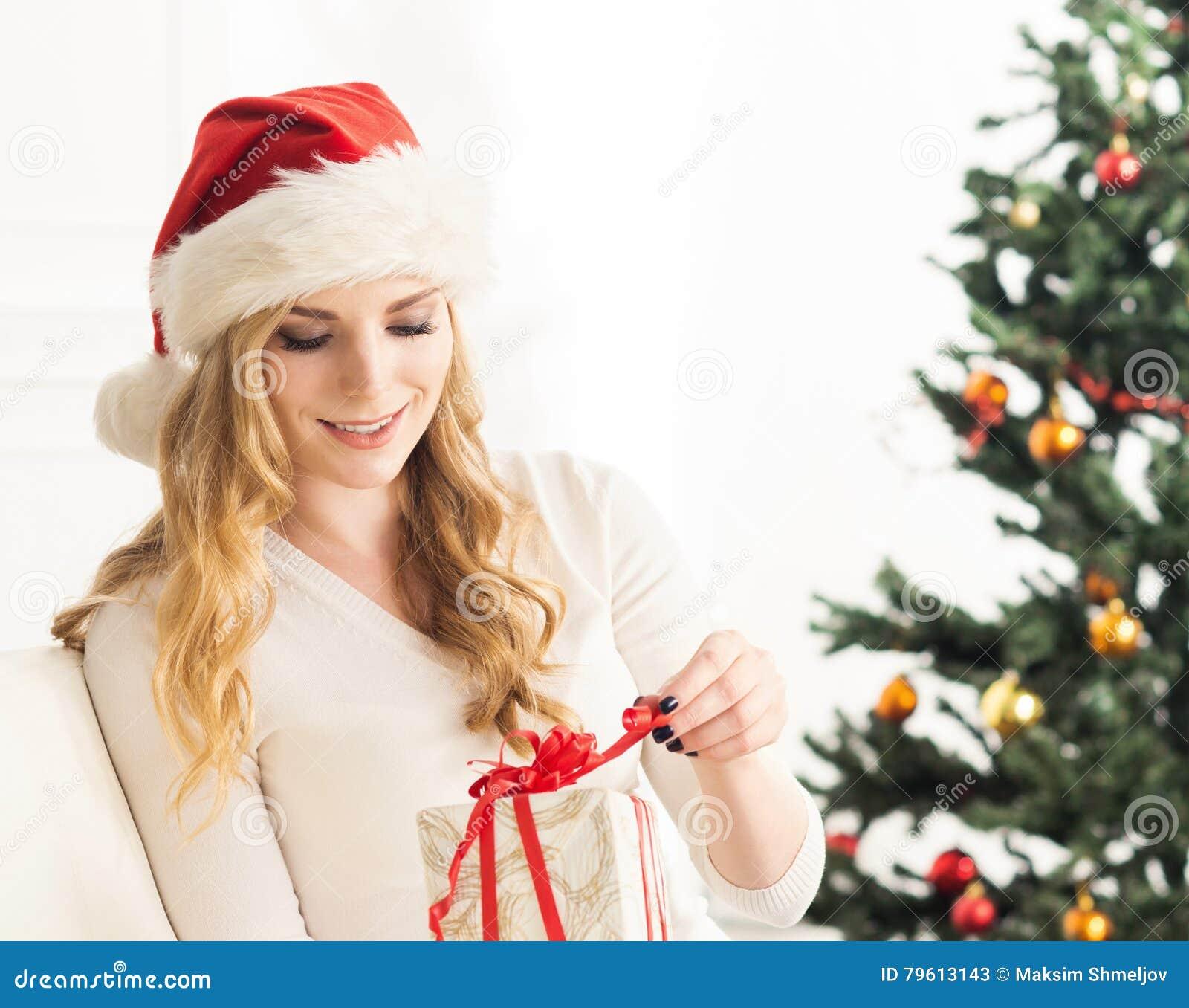 Retrato de uma mulher nova em um chapéu do Natal que prende um presente