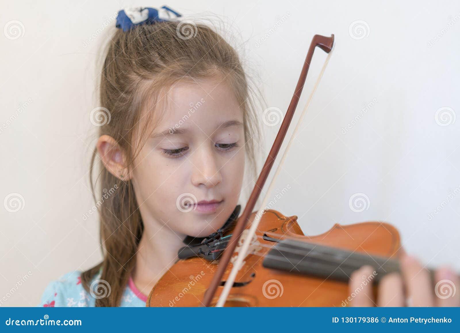 Retrato de un adolescente rubio joven que toca el violín Muchacha que toca el violín en un fondo ligero