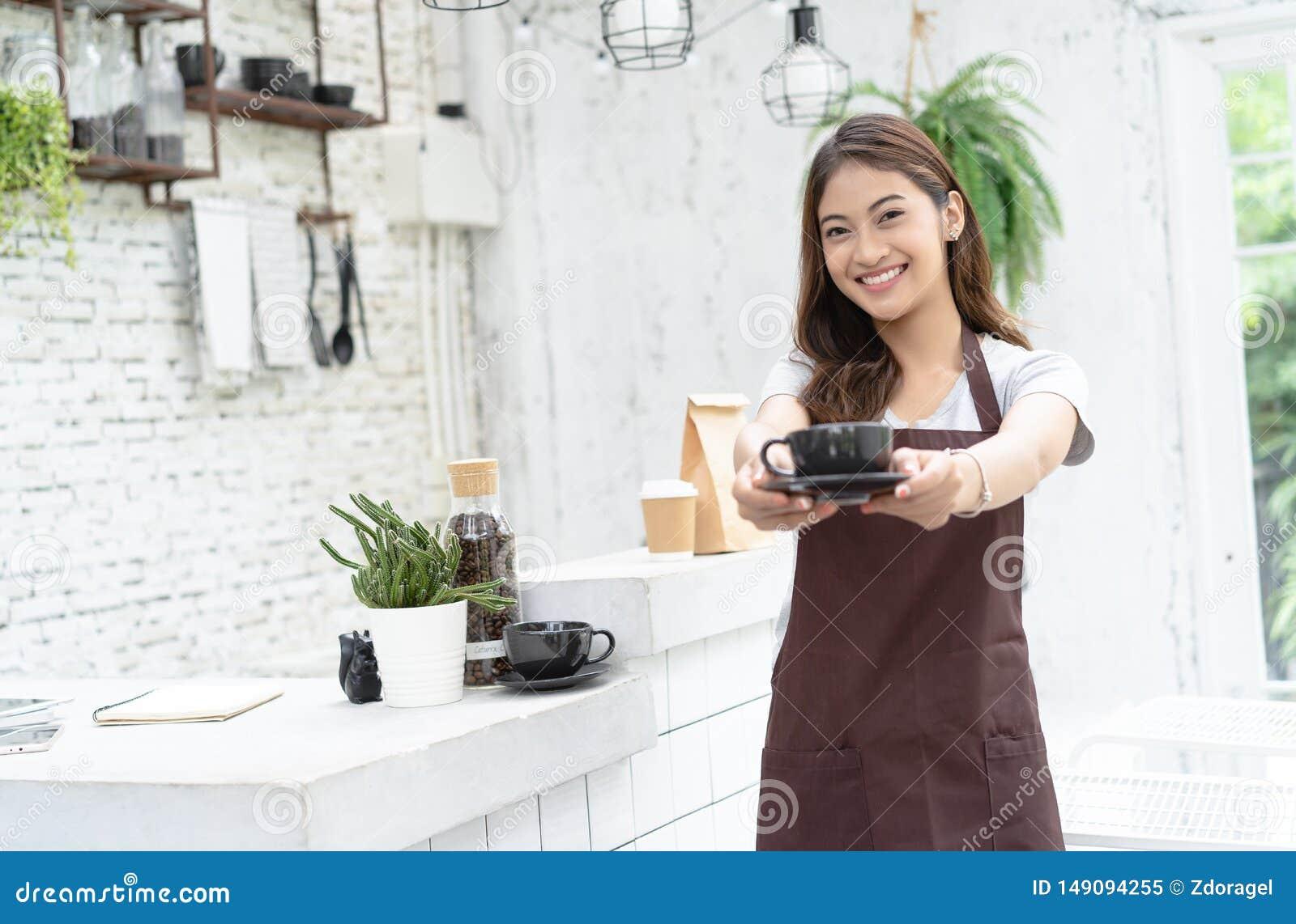 Retrato de un barista asiático joven sonriente en el delantal que sonríe y que ofrece una taza de café encendido al lado de la má