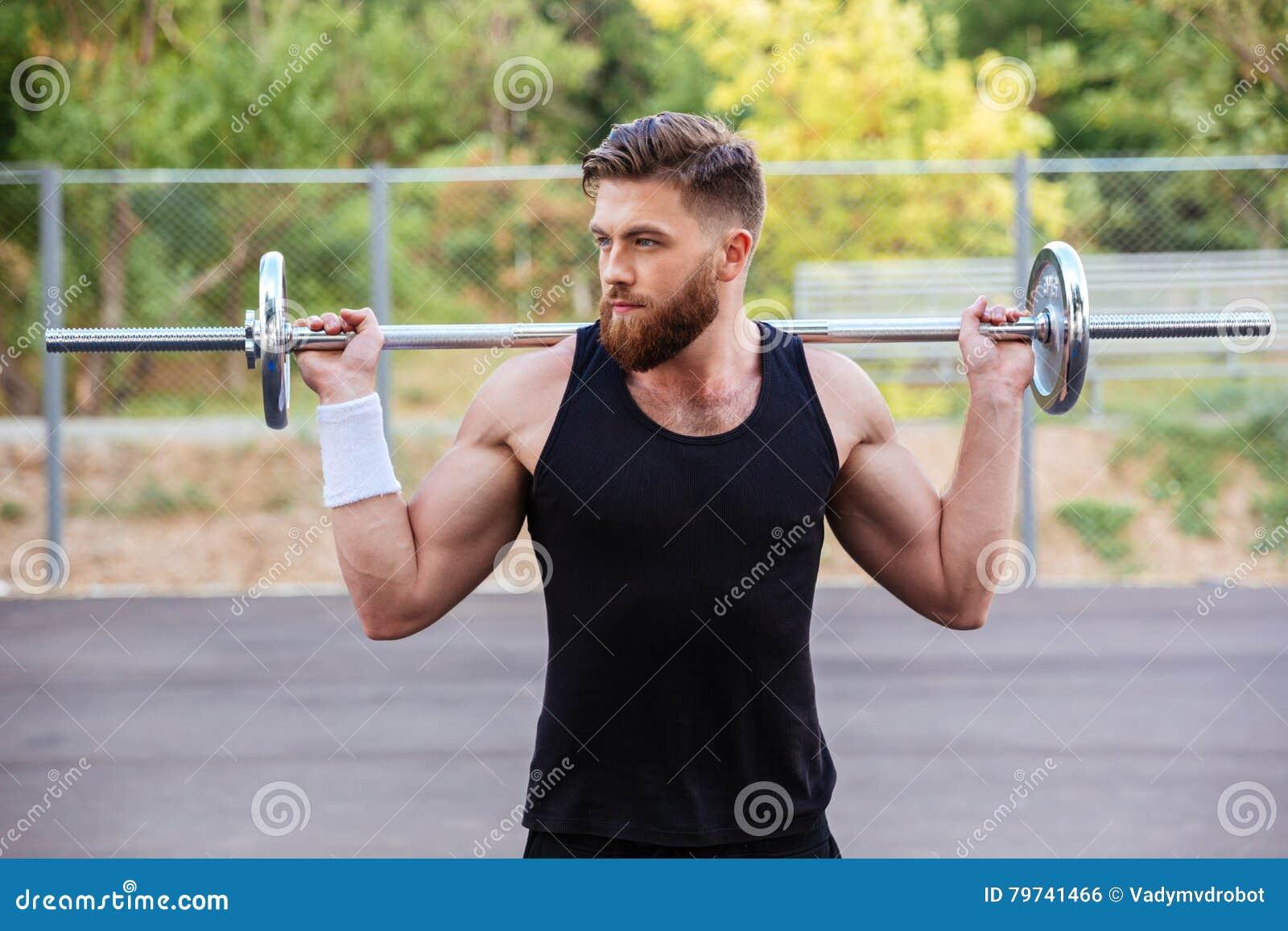 Retrato de un entrenamiento muscular del hombre con el barbell