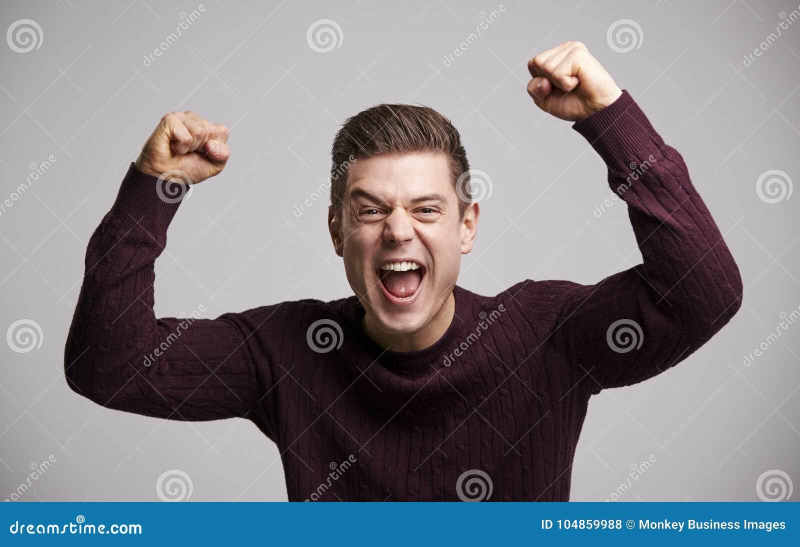 Retrato de un hombre blanco joven de celebración con los brazos para arriba
