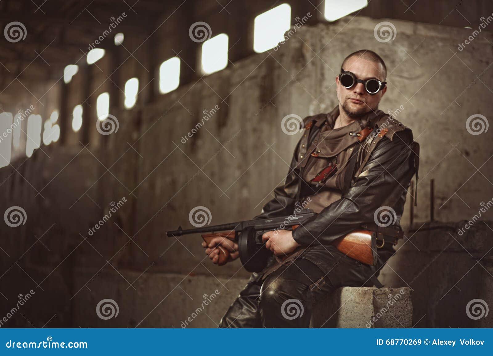 Retrato de un hombre del mundo posts-apocalíptico con la ametralladora y los vidrios negros en un edificio abandonado