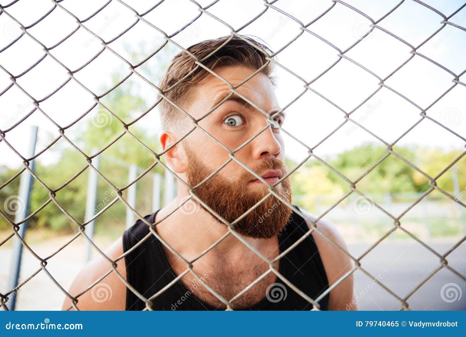 Retrato de un hombre divertido que mira a través de la cerca del metal