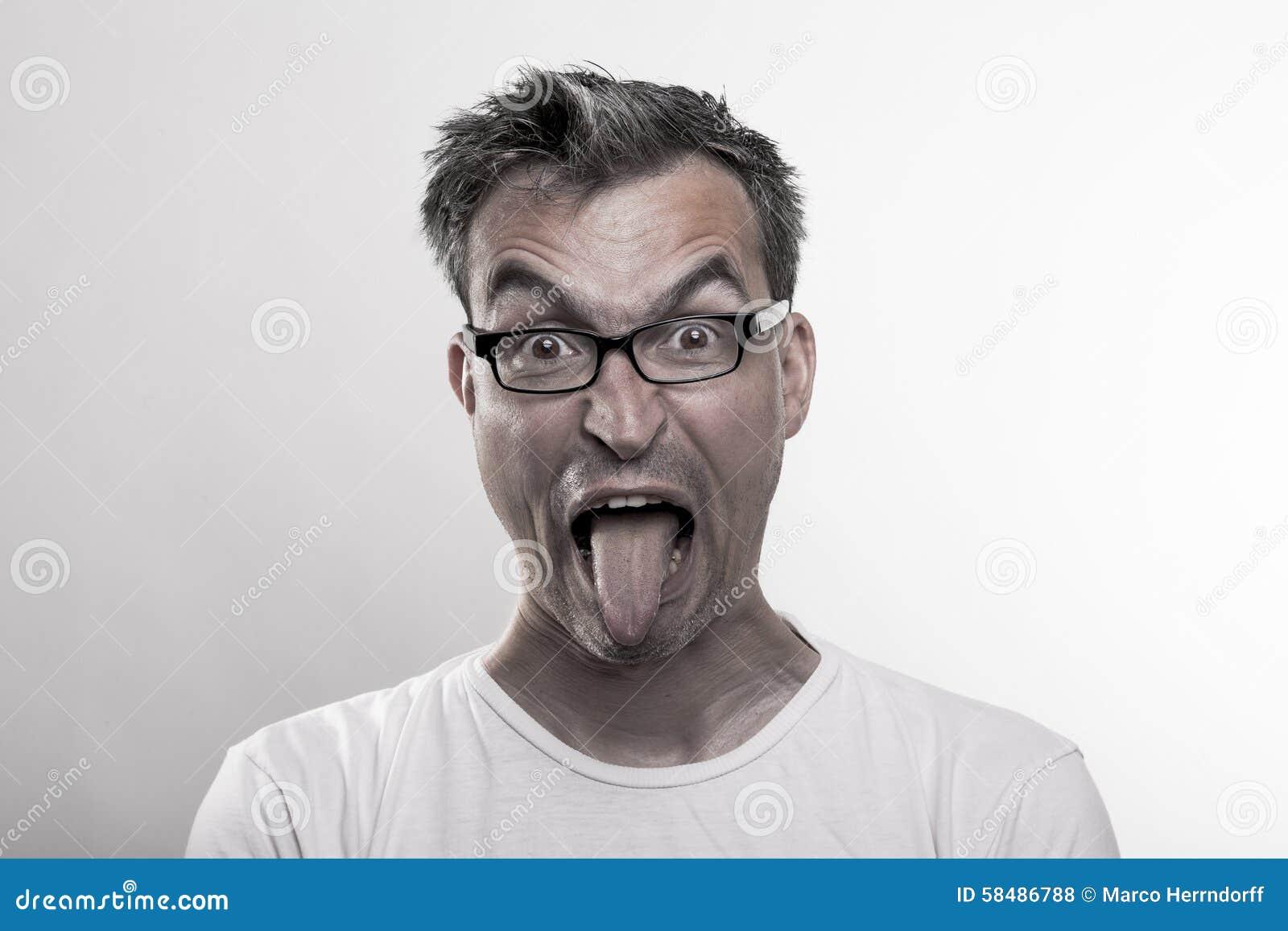 Retrato de un hombre en el repugnancia que empuja hacia fuera su lengua