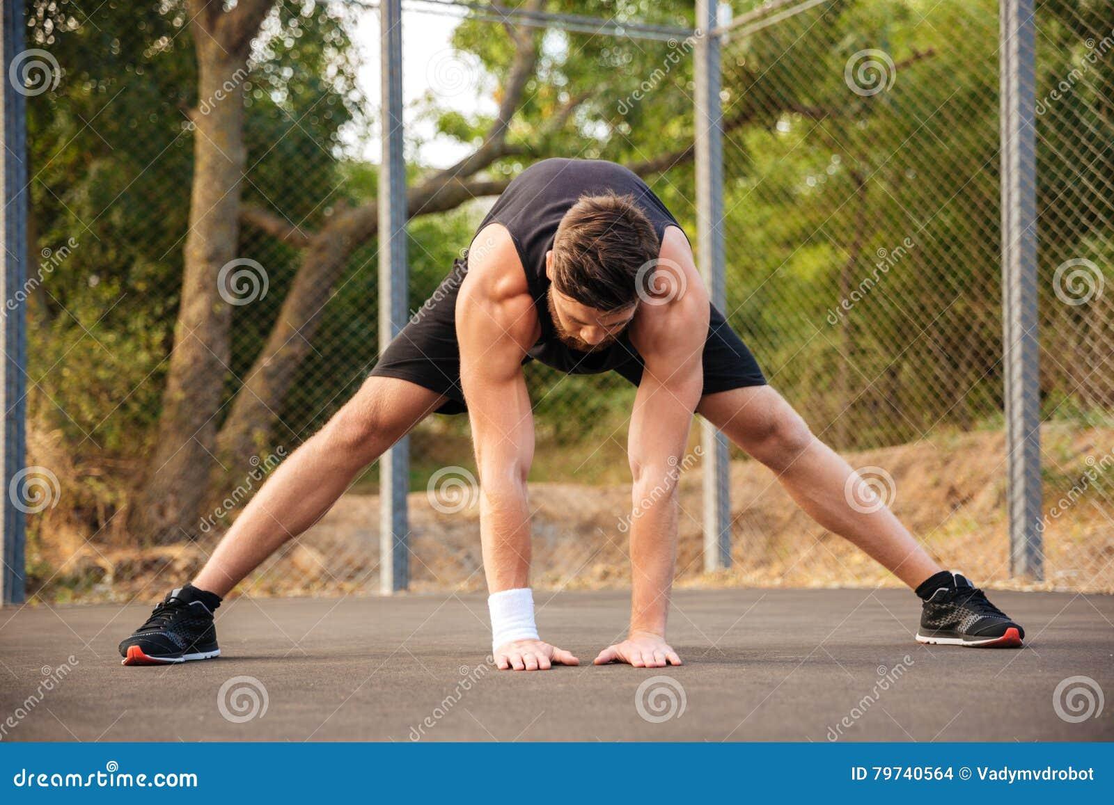 Retrato de un hombre en la ropa de deportes que estira las piernas al aire libre
