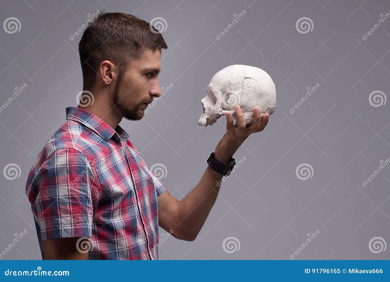 Retrato de un hombre en perfil con un cráneo en su mano