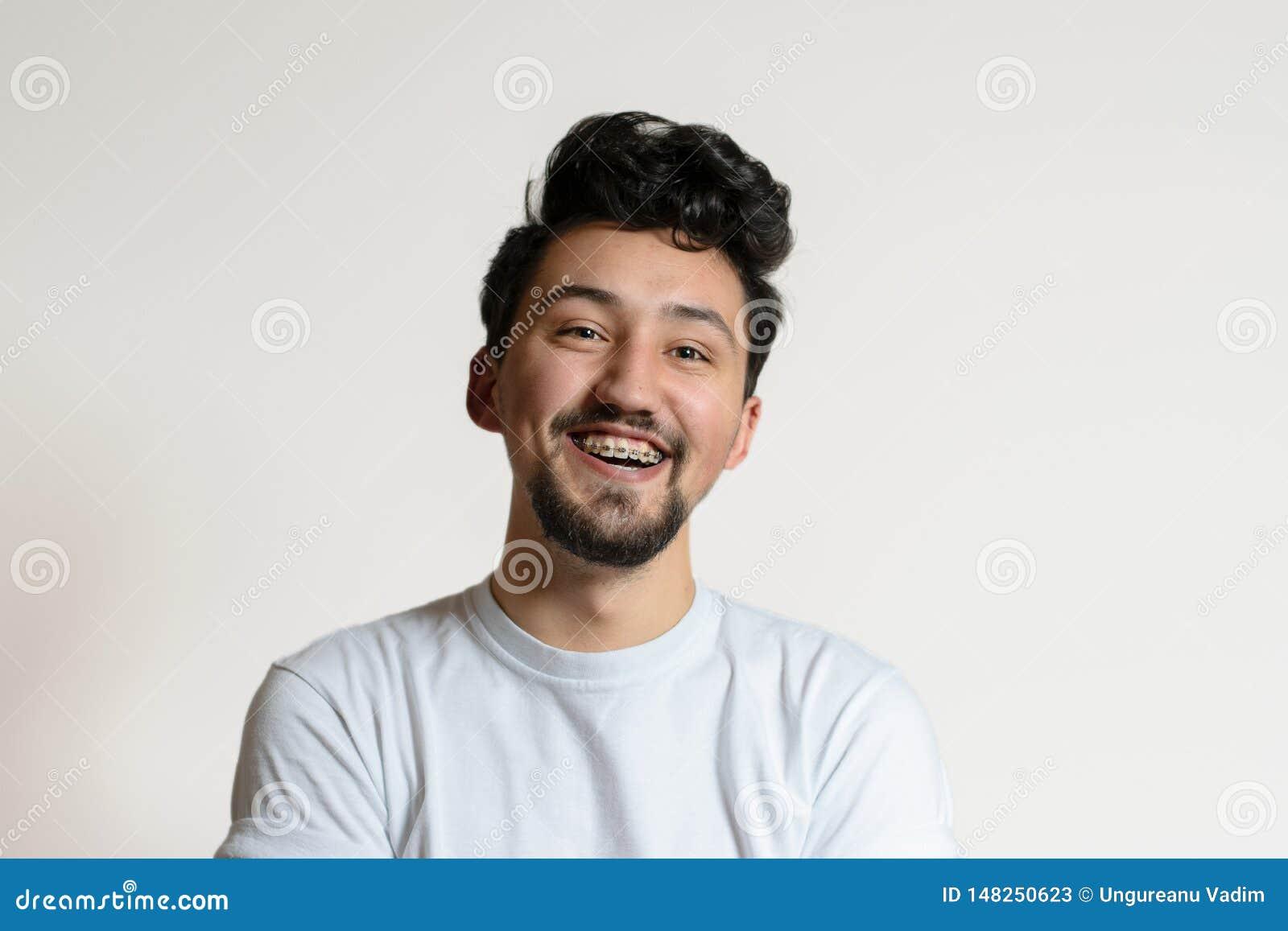 Retrato de un hombre joven con los apoyos que sonr?e y que r?e Un hombre joven feliz con los apoyos en un fondo blanco