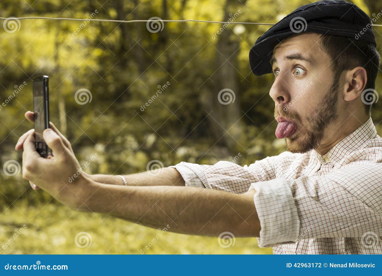 Retrato de un hombre joven loco con el casquillo que toma un selfie