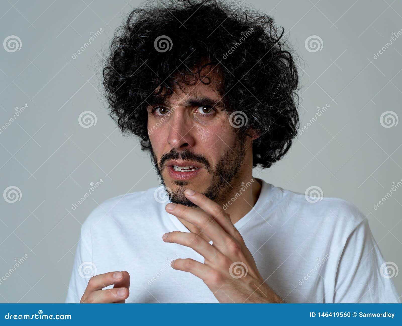 Retrato de un hombre joven que considera chocado y disgustado algo Expresiones y emociones humanas