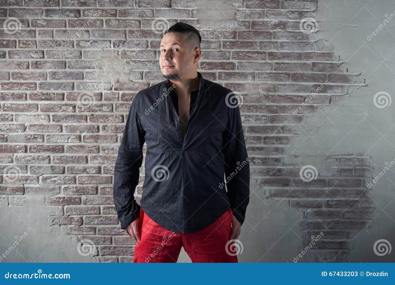 Retrato de un hombre joven, rechoncho, vestido en holguras rojas y una camisa negra