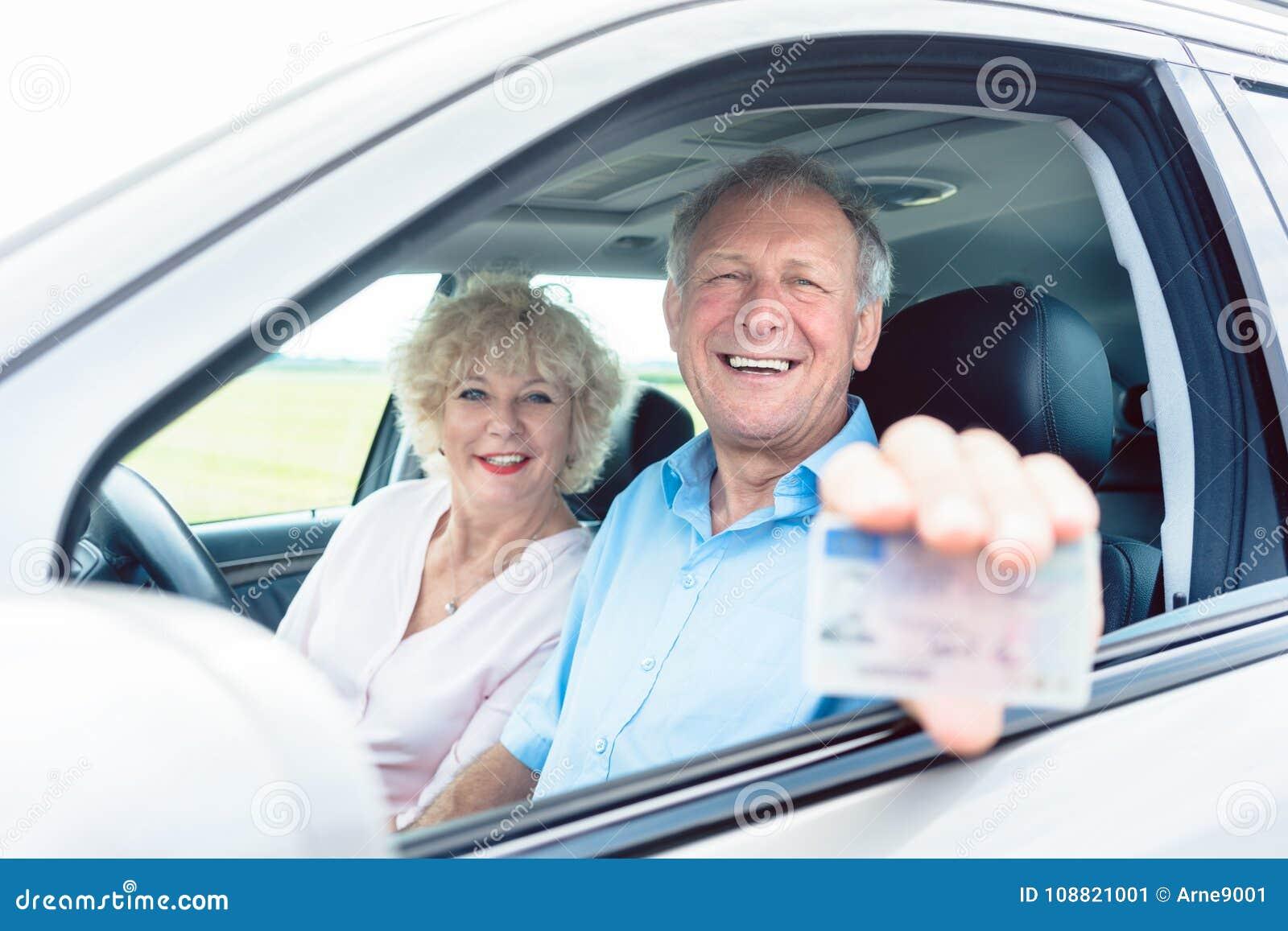 Retrato de un hombre mayor feliz que muestra su carné de conducir mientras que