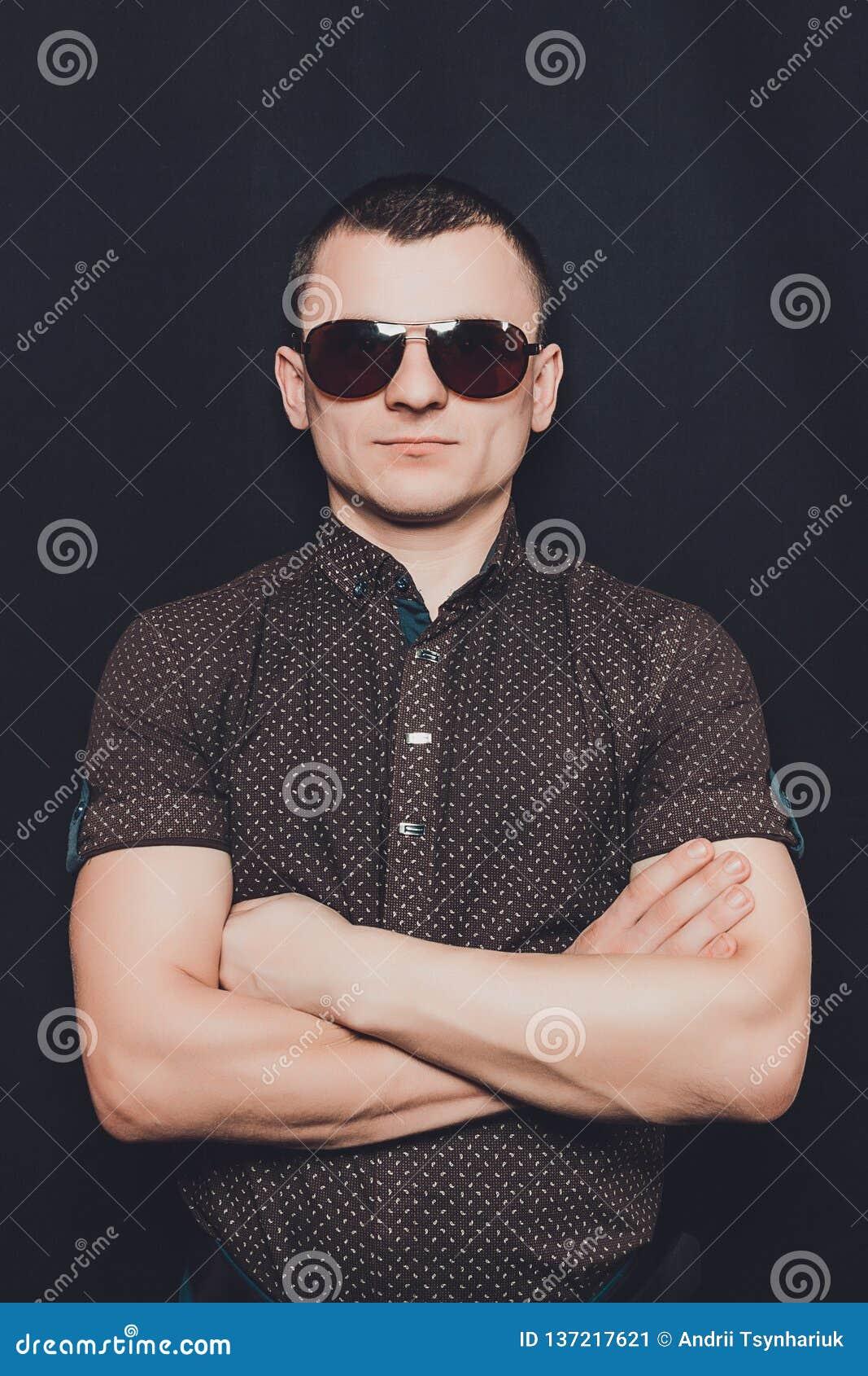 Retrato de un hombre vestido en una camisa negra y gafas de sol marrones